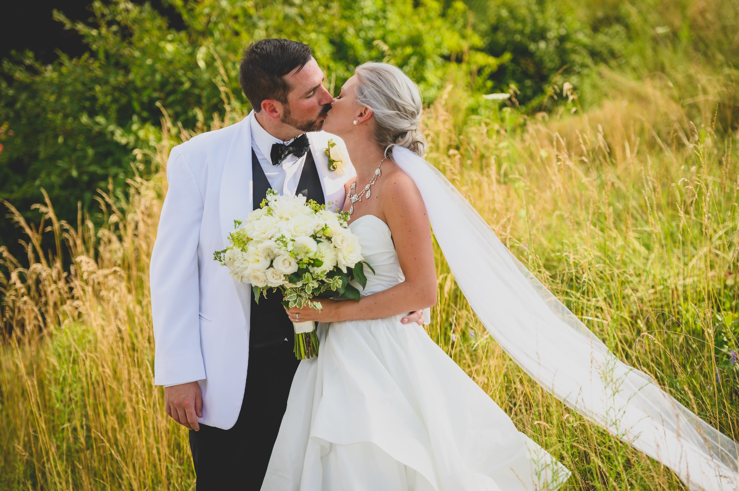 A groom in a white tuxedo kissing his bride in front of stalks of grain.