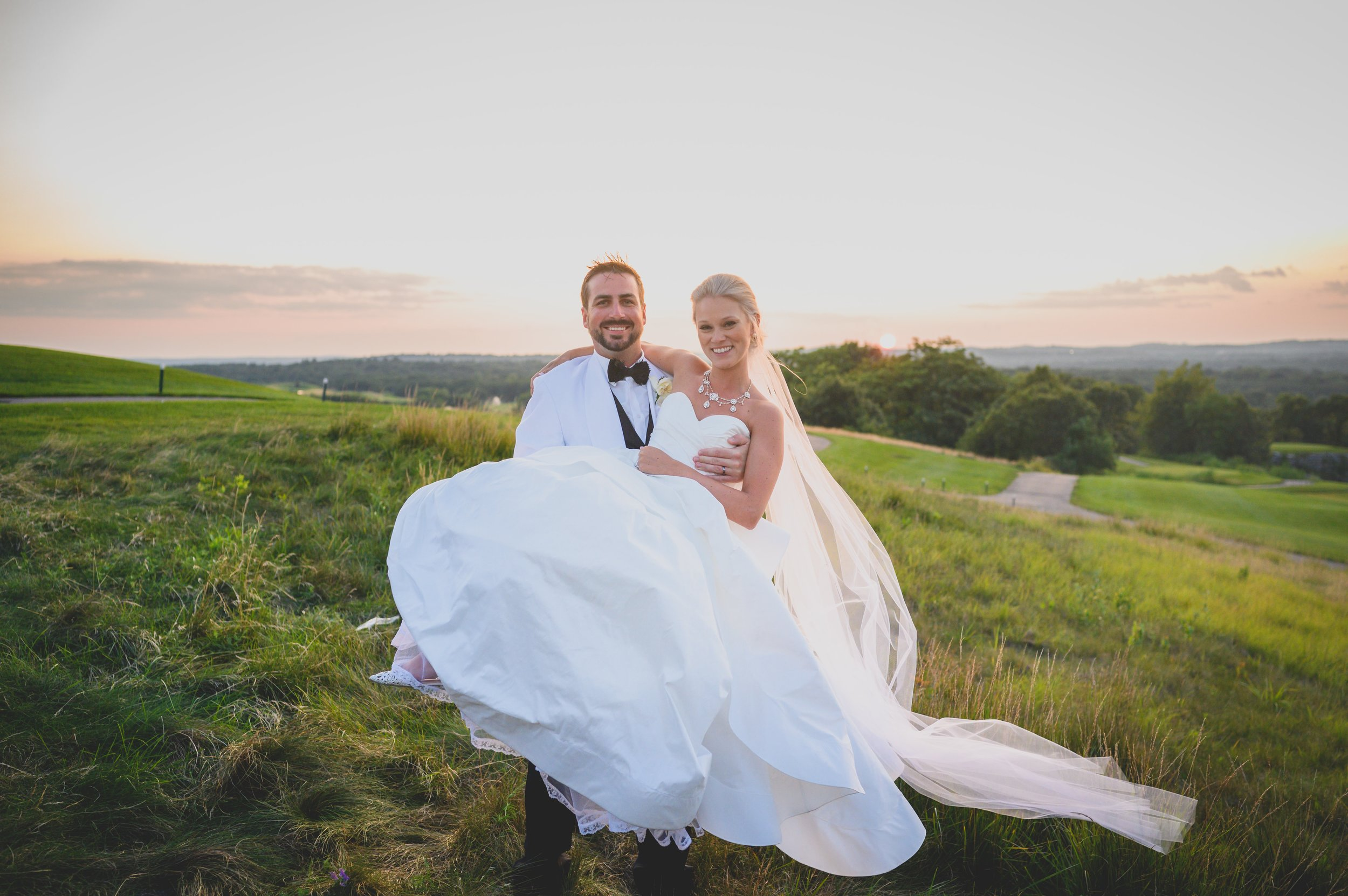 A groom in a white tuxedo holding his bride in his arms on a green golf course.