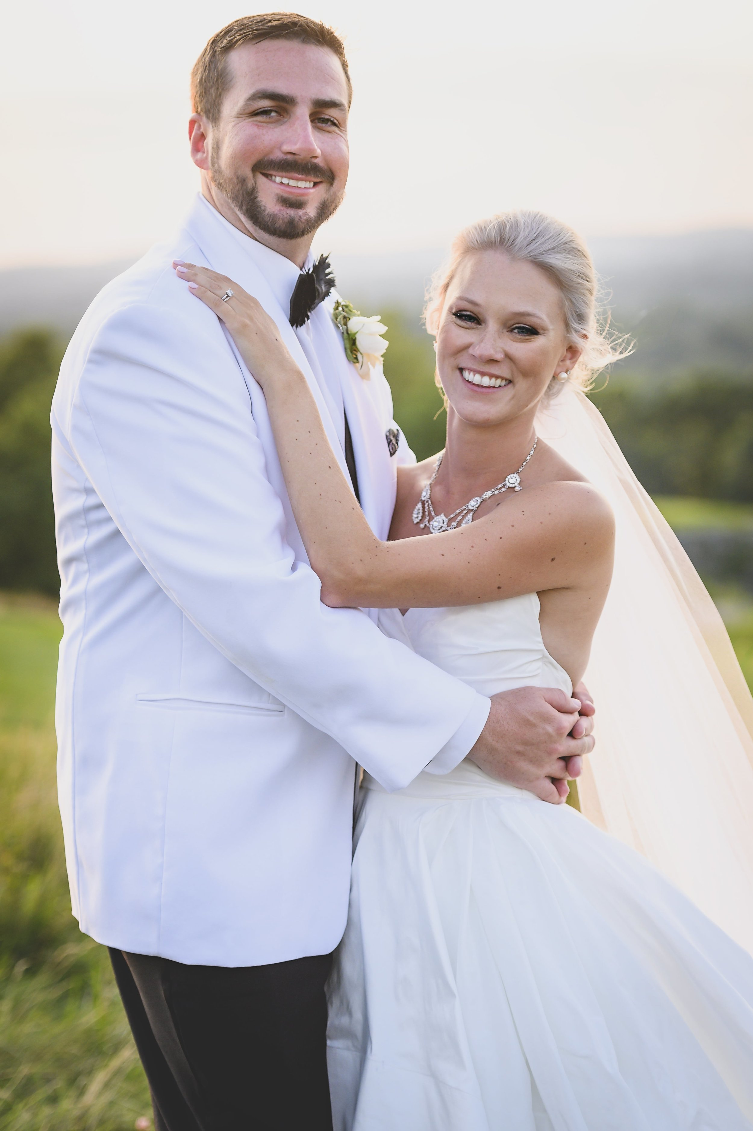 A smiling bride and groom in white.