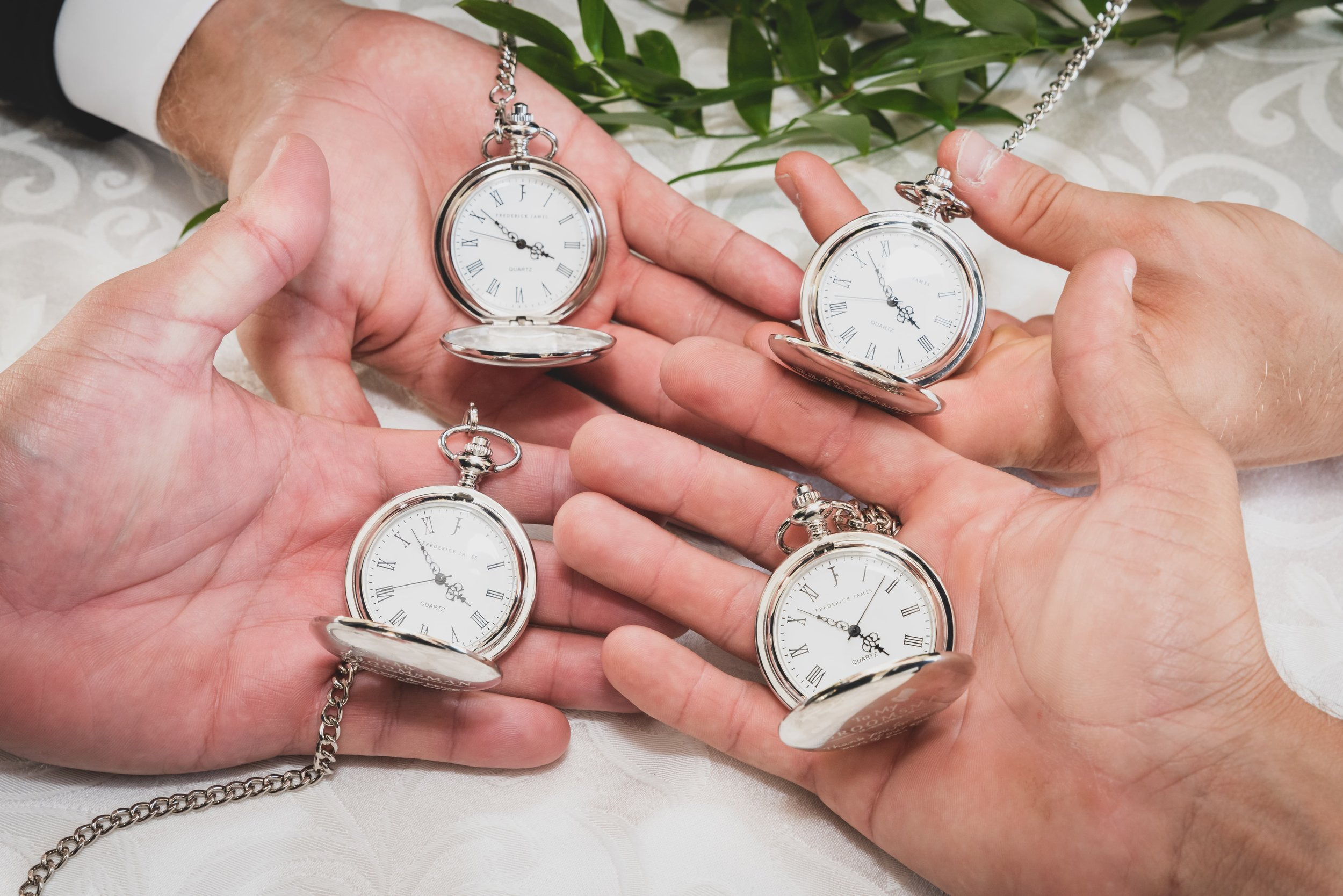 Four groomsman hands holding identical pocket watches.