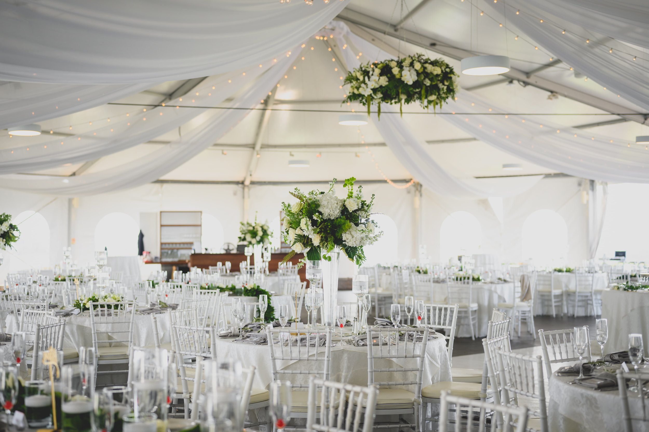 A outdoor wedding reception area under a large tent.