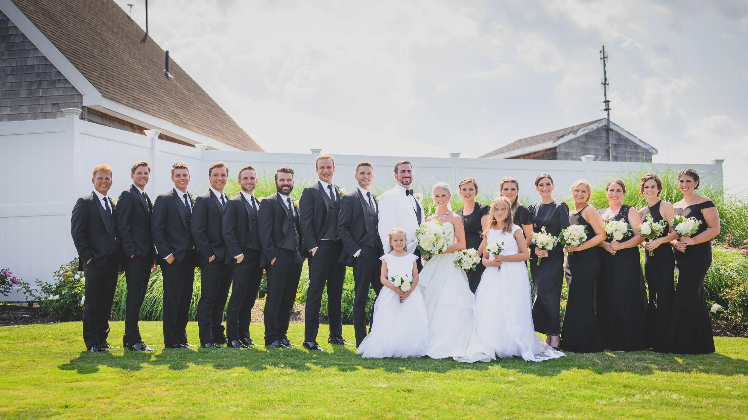 A smiling bridal party outdoors on a green lawn.
