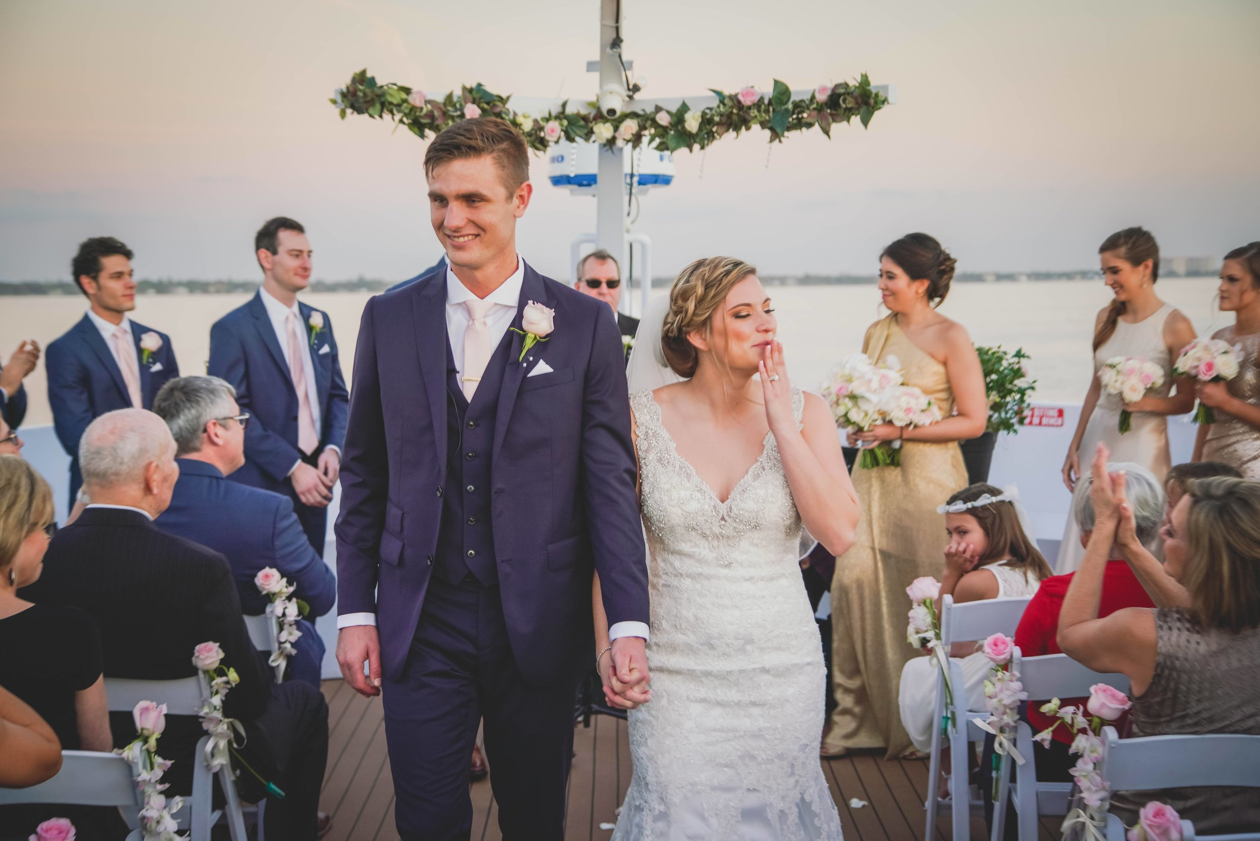 A newlywed couple exit their wedding ceremony on the deck of a yacht.