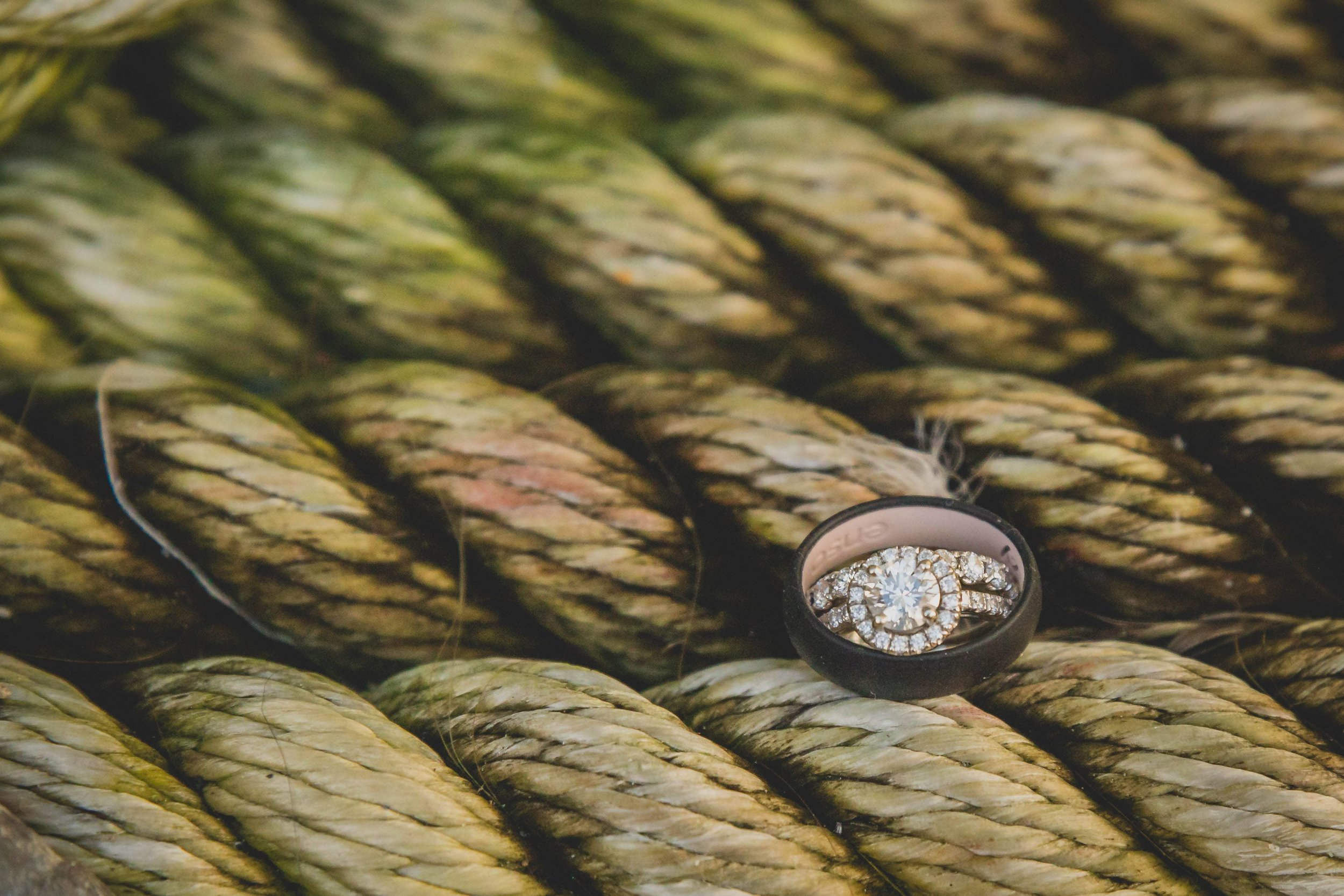 Wedding bands perched on the thick rope of ship.
