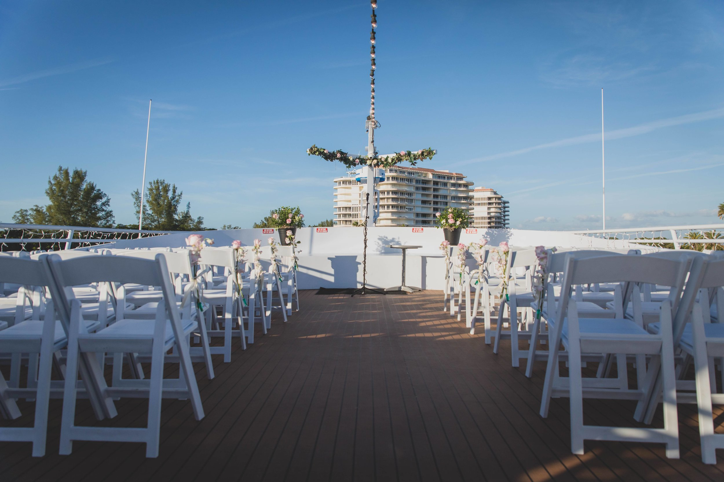 An open sky nautical wedding ceremony on the deck of a ship/yacht.
