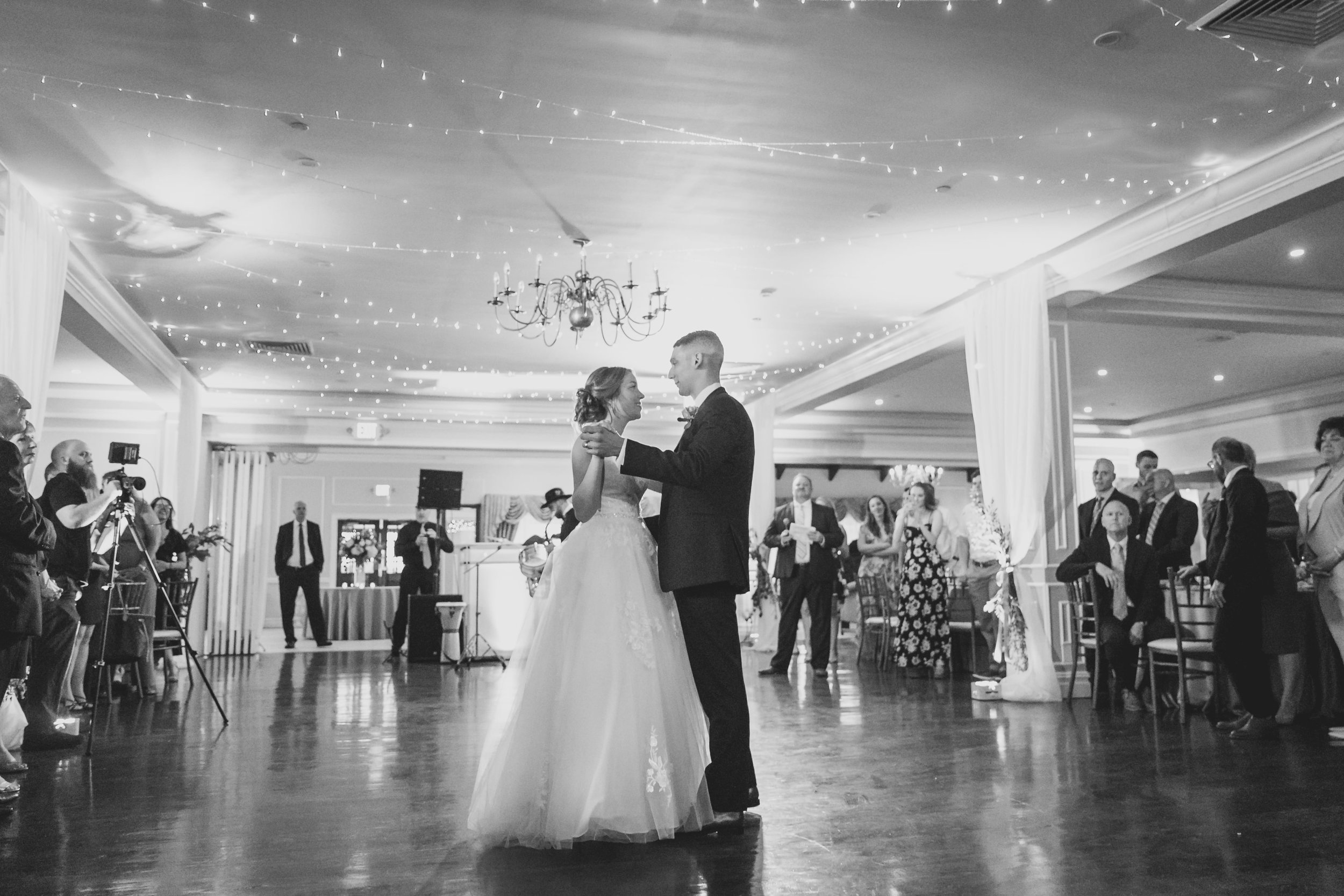 Bride and groom sharing their first dance in a ballroom surrounded by guests.