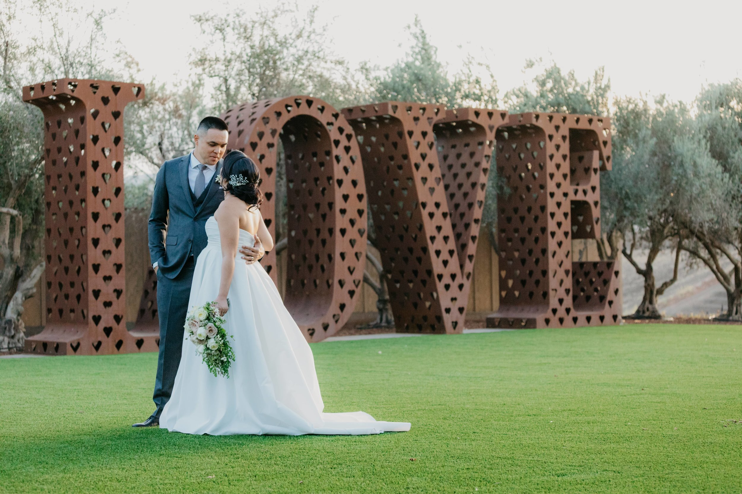 Bride and groom on a field of green in front of a giant 3-d love sign.
