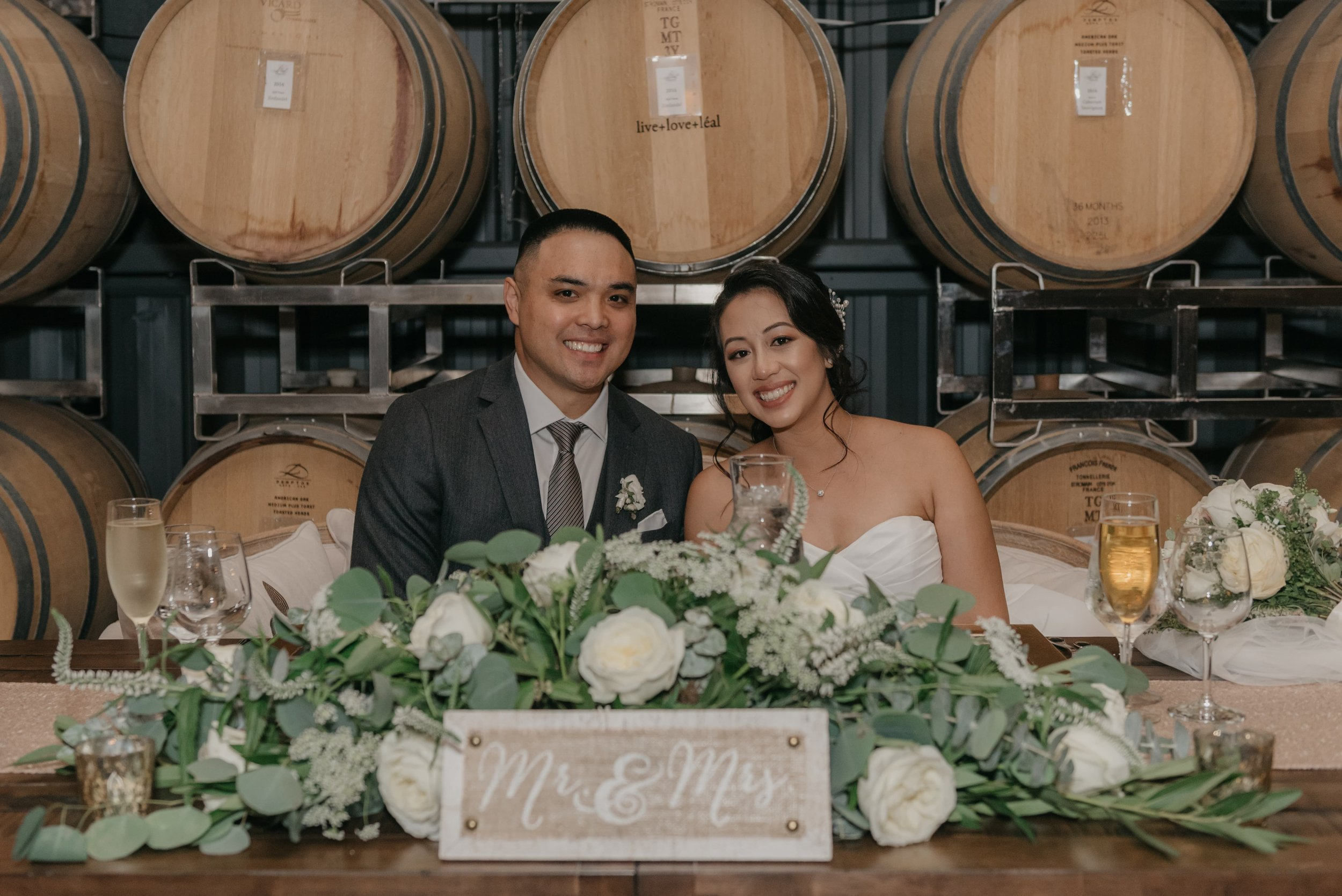 Married couple sitting at wedding reception table in front of wine barrels.