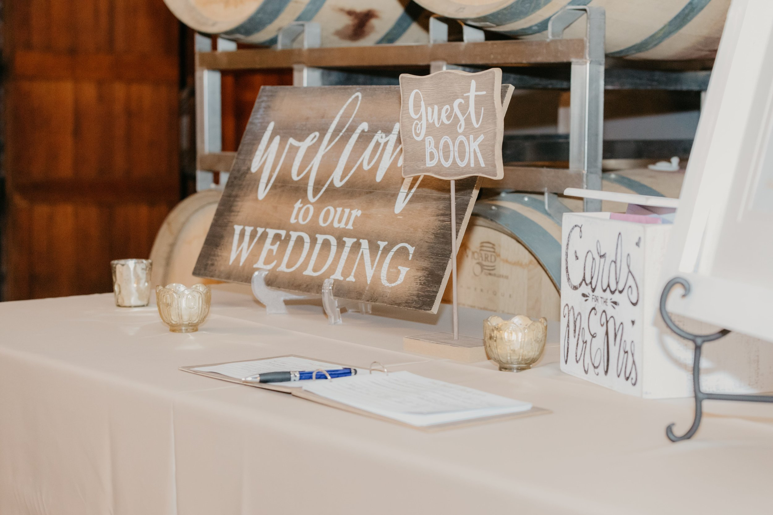 Wedding reception table decorated with wood accents to match their vineyard wine barrel theme.