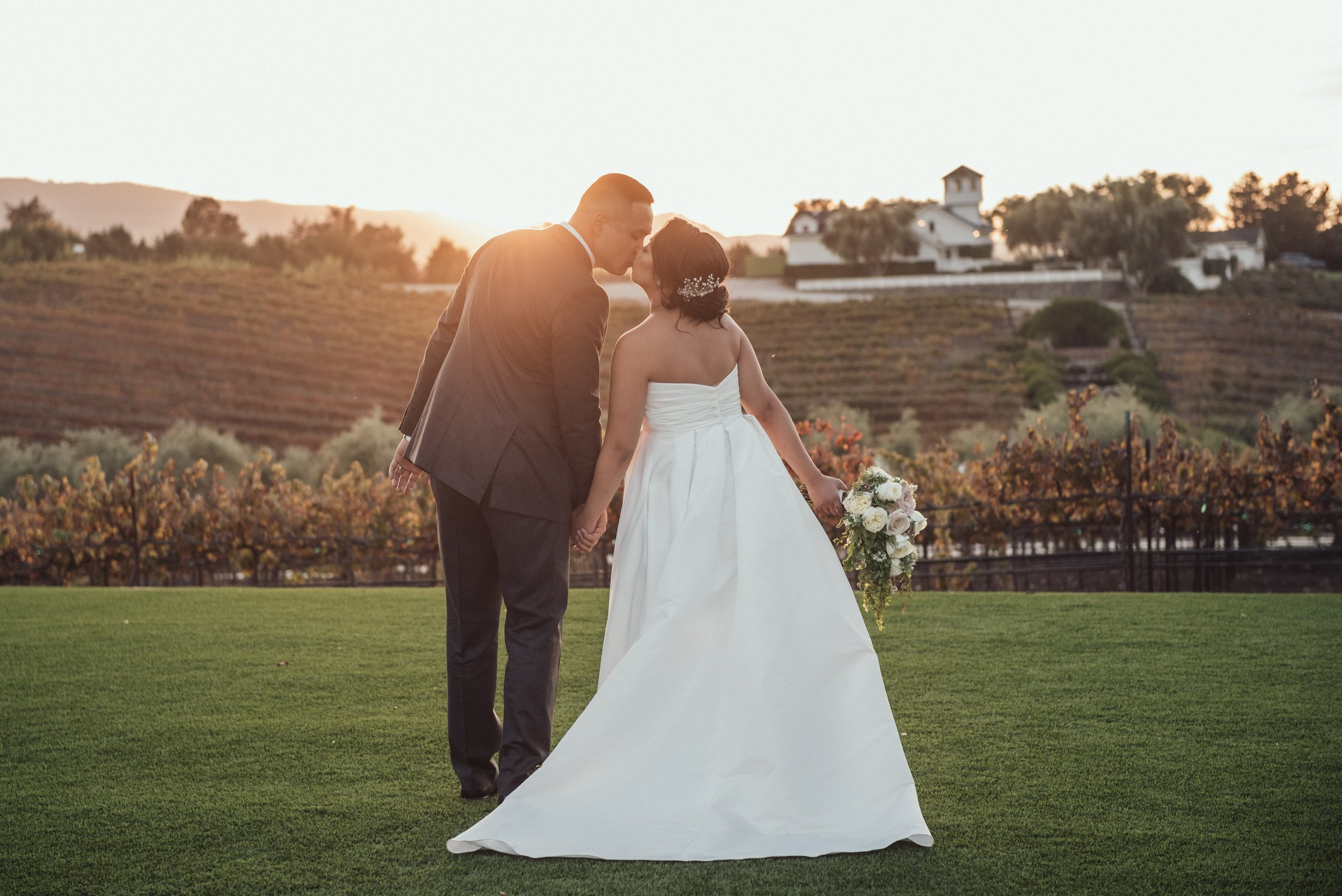 Newlywed couple kissing outdoors with the sun setting at the Leal Vineyards.