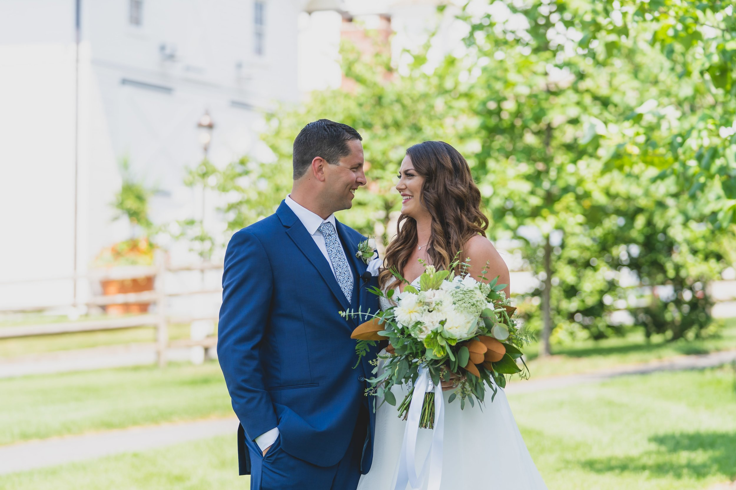 Bride and groom smiling at one another outside their venue on a sunny summer day.