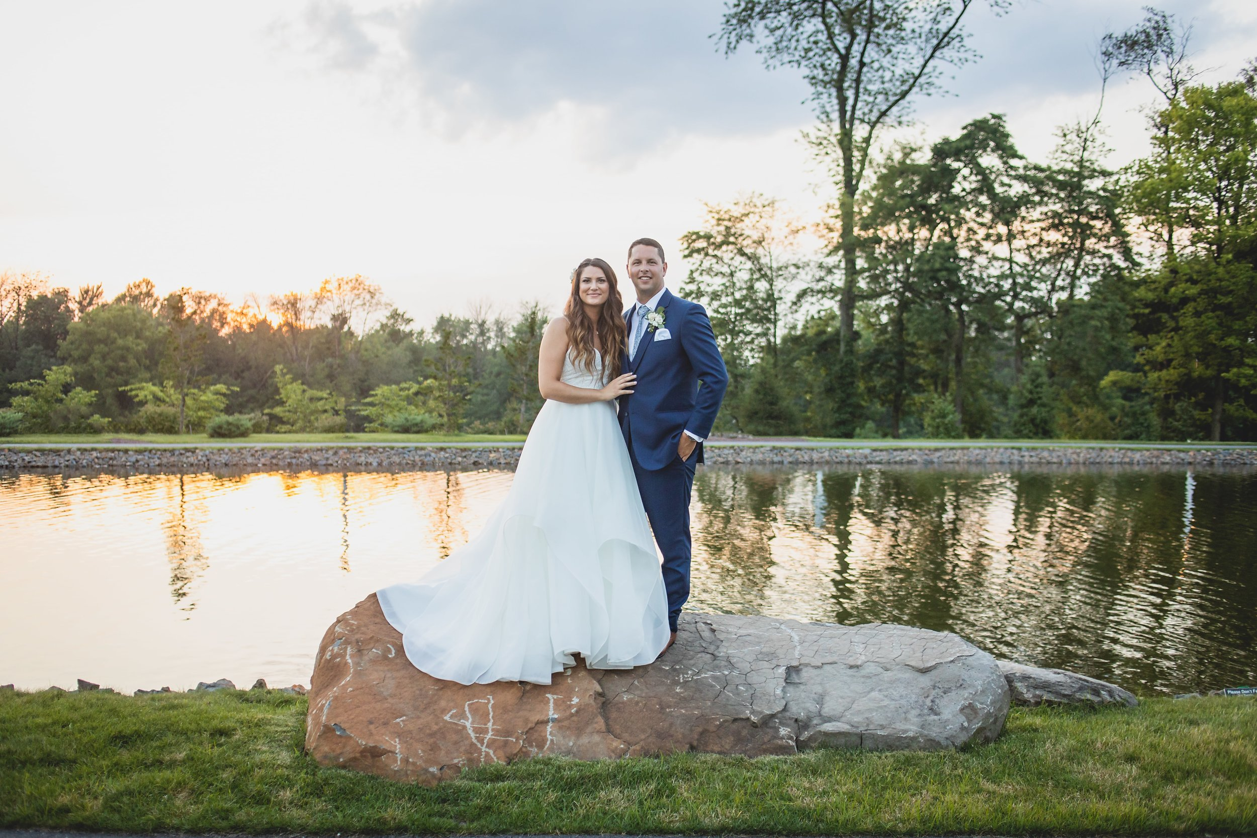 Bride and groom standing on a large rock with sunlight reflecting off the pond behind them.