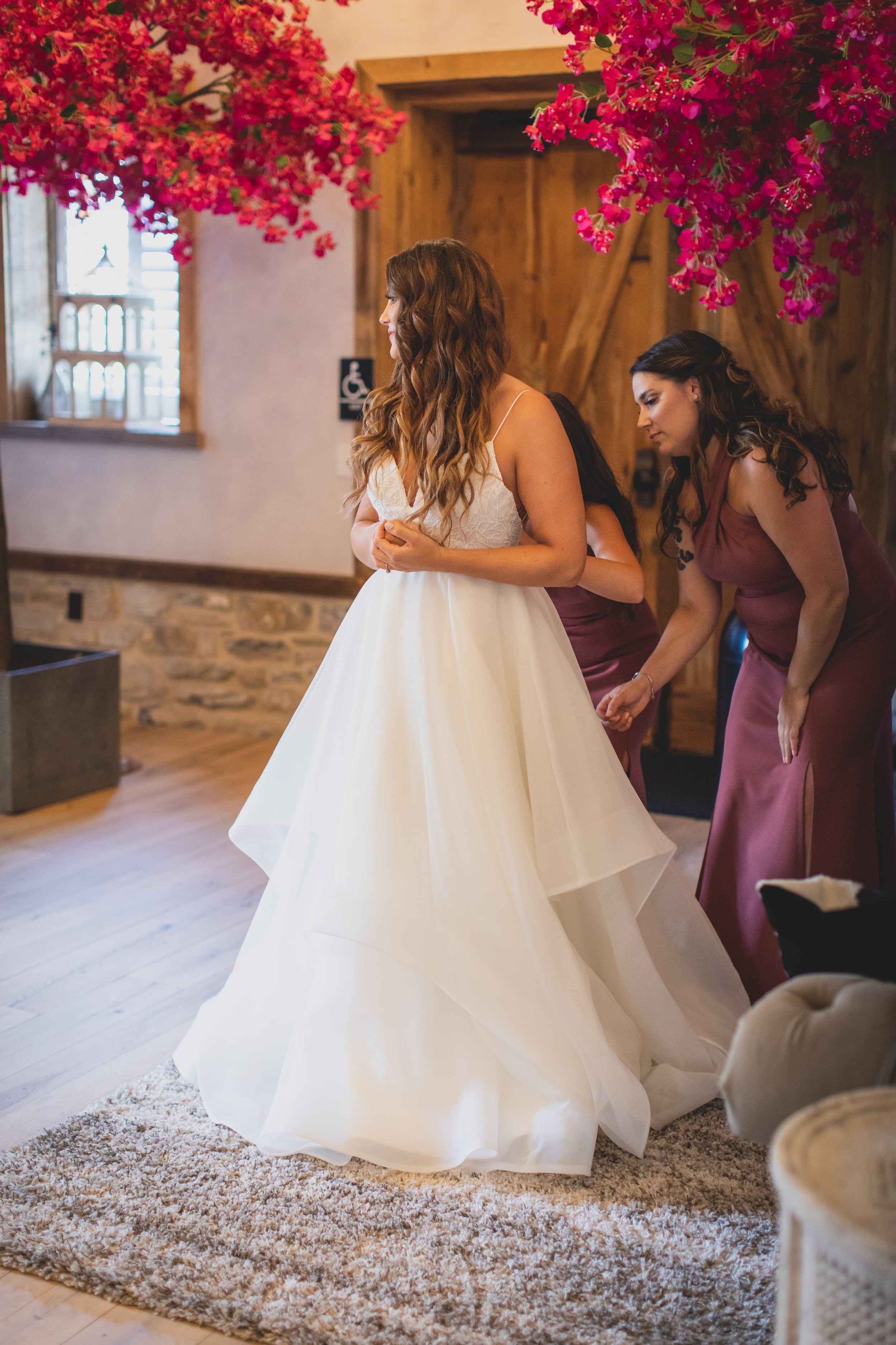 Bride in her bridal suite getting her wedding dress zipped by her bridesmaids.