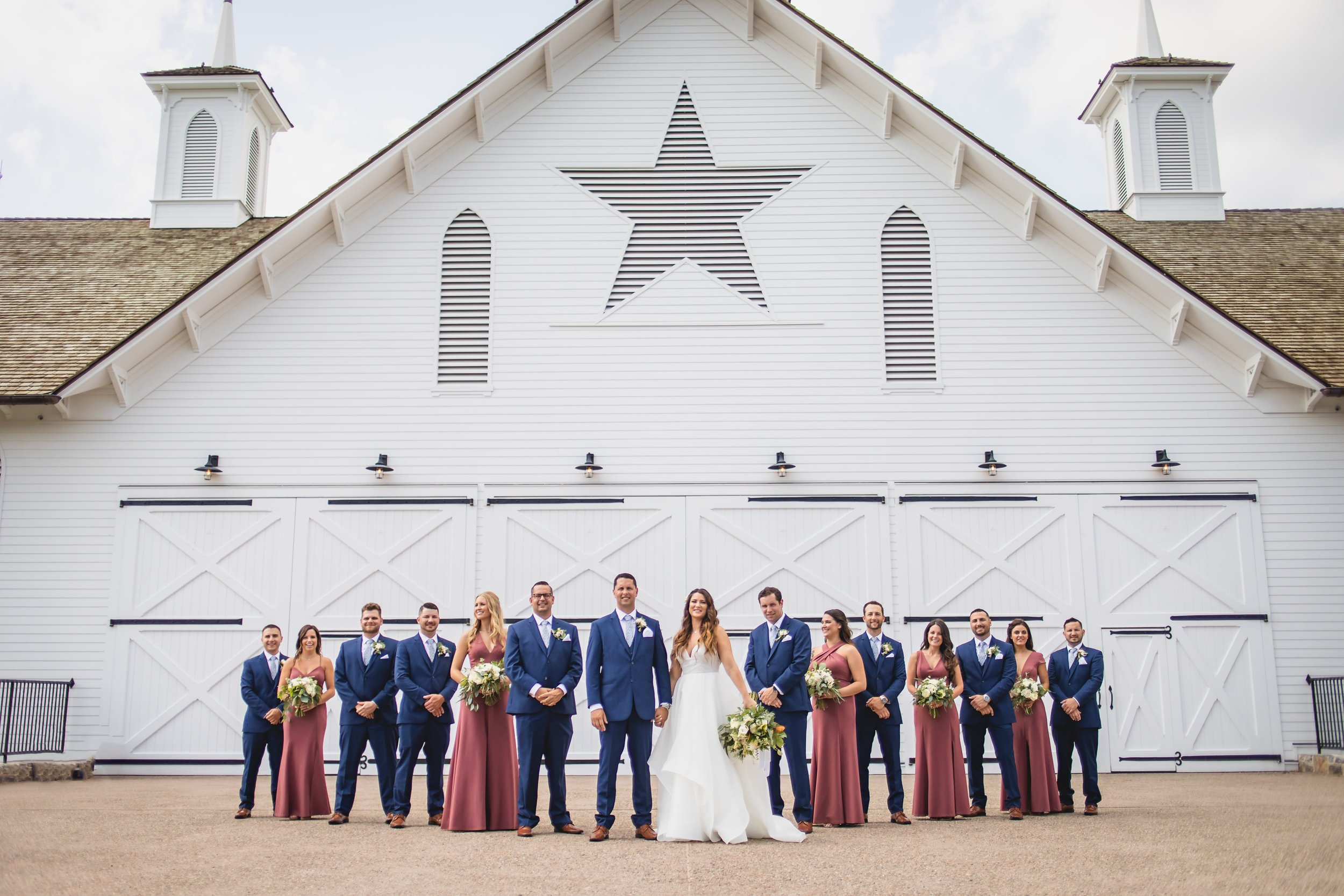 The bridal party standing in a V-formation in front of the star barn wedding venue.