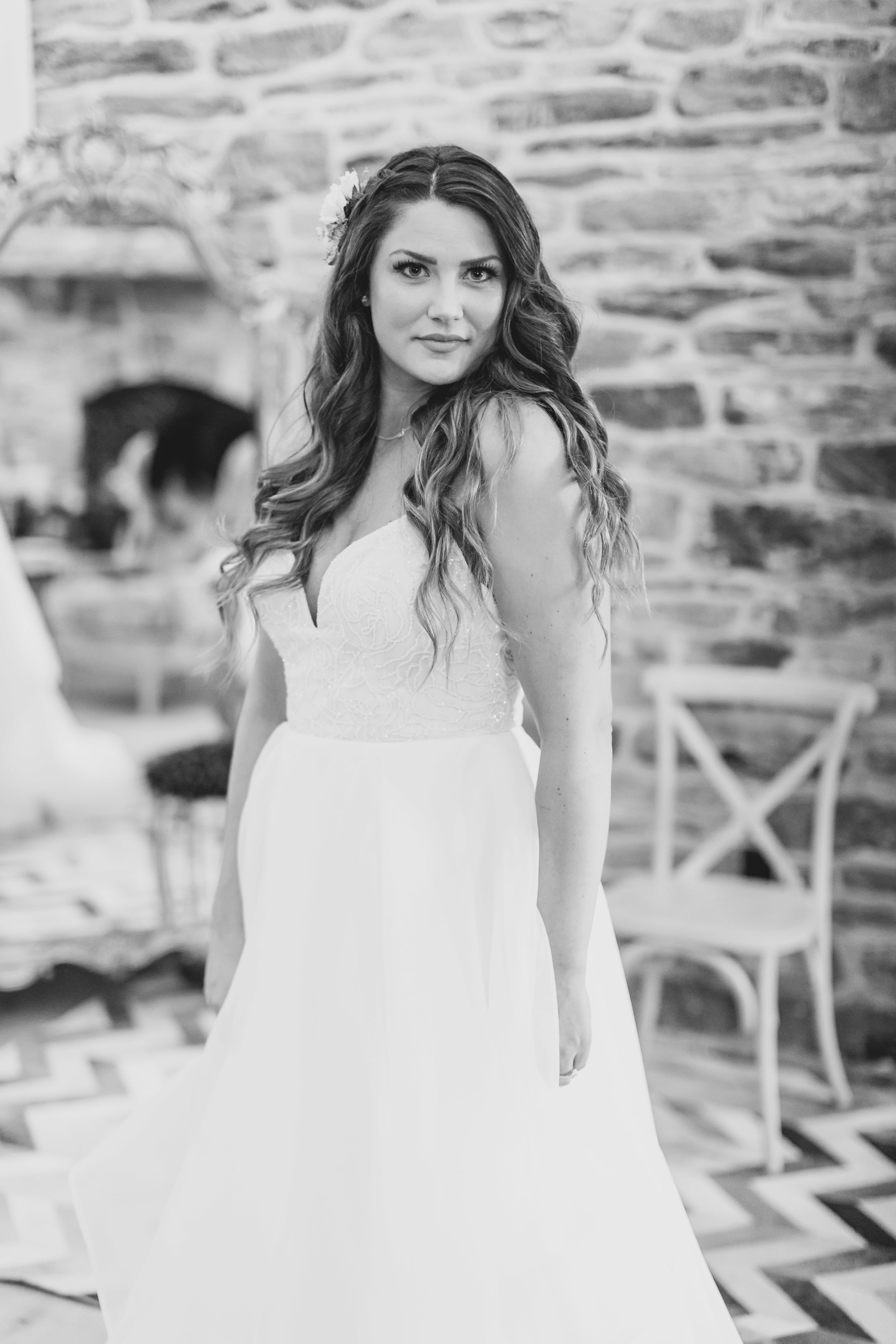 Black and white of the bride staring into the camera with her wavy hair cascading down her shoulders.