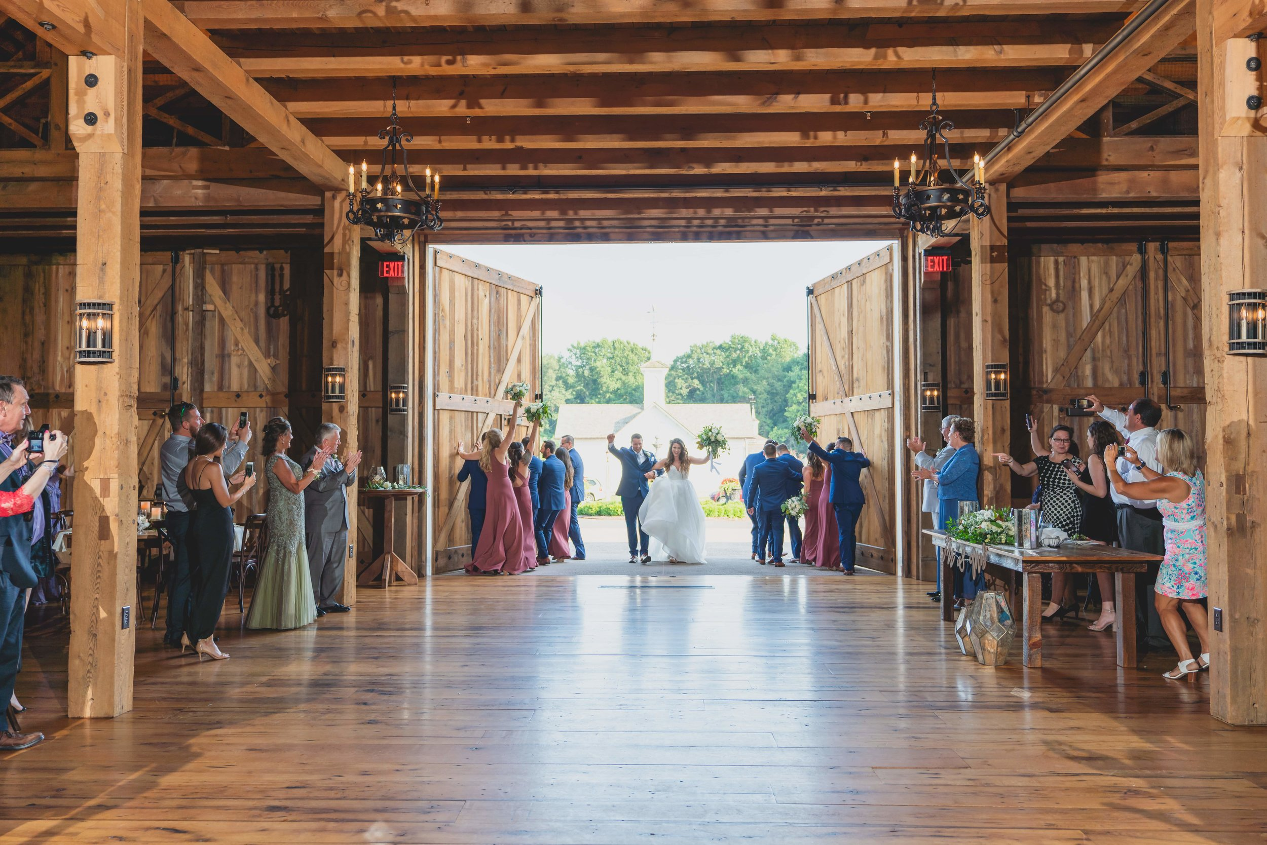 The bride and groom entering their reception, held in a large renovated barn, to the applause of their guests.