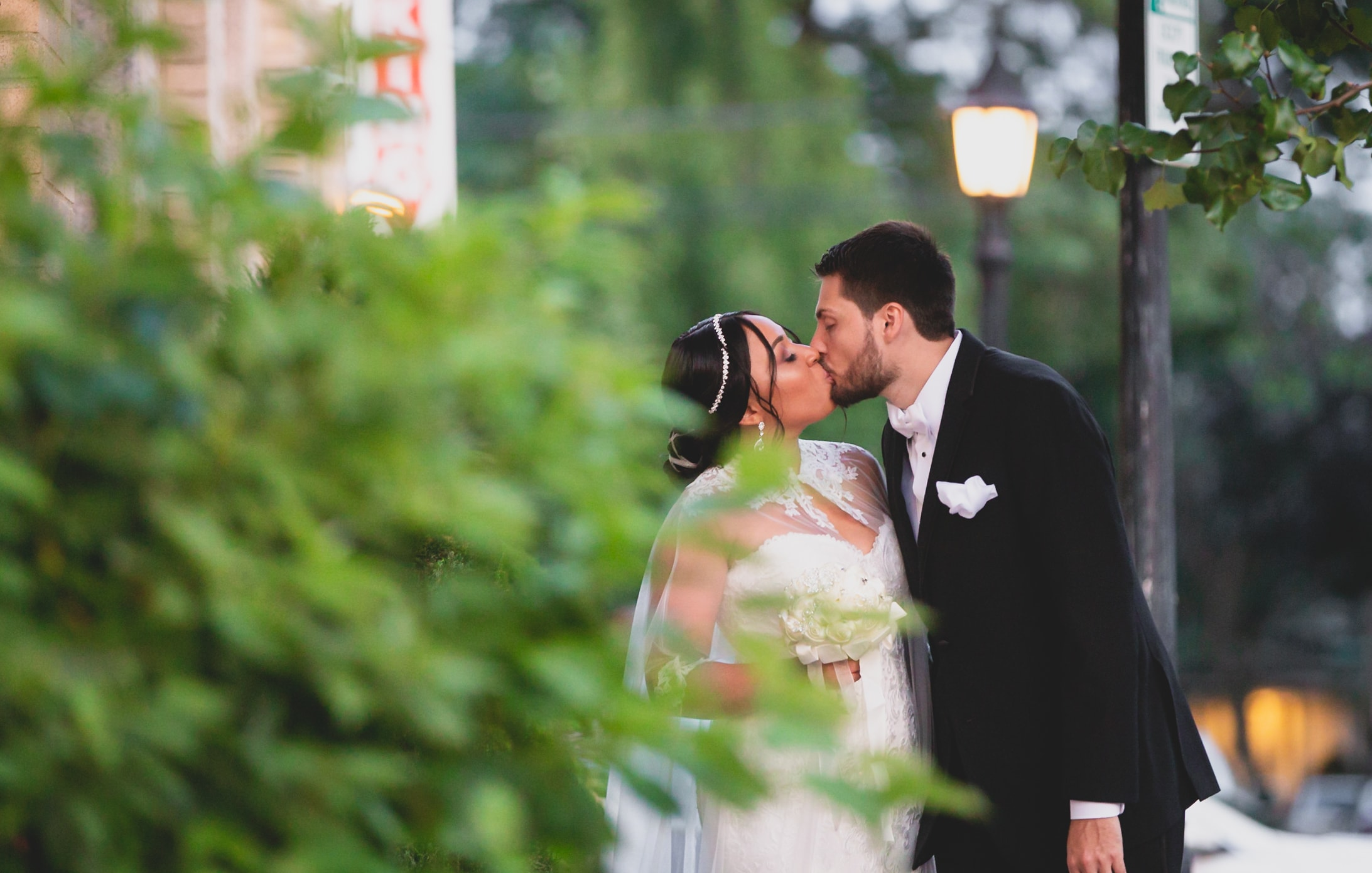Bride and groom kissing under a streetlight.