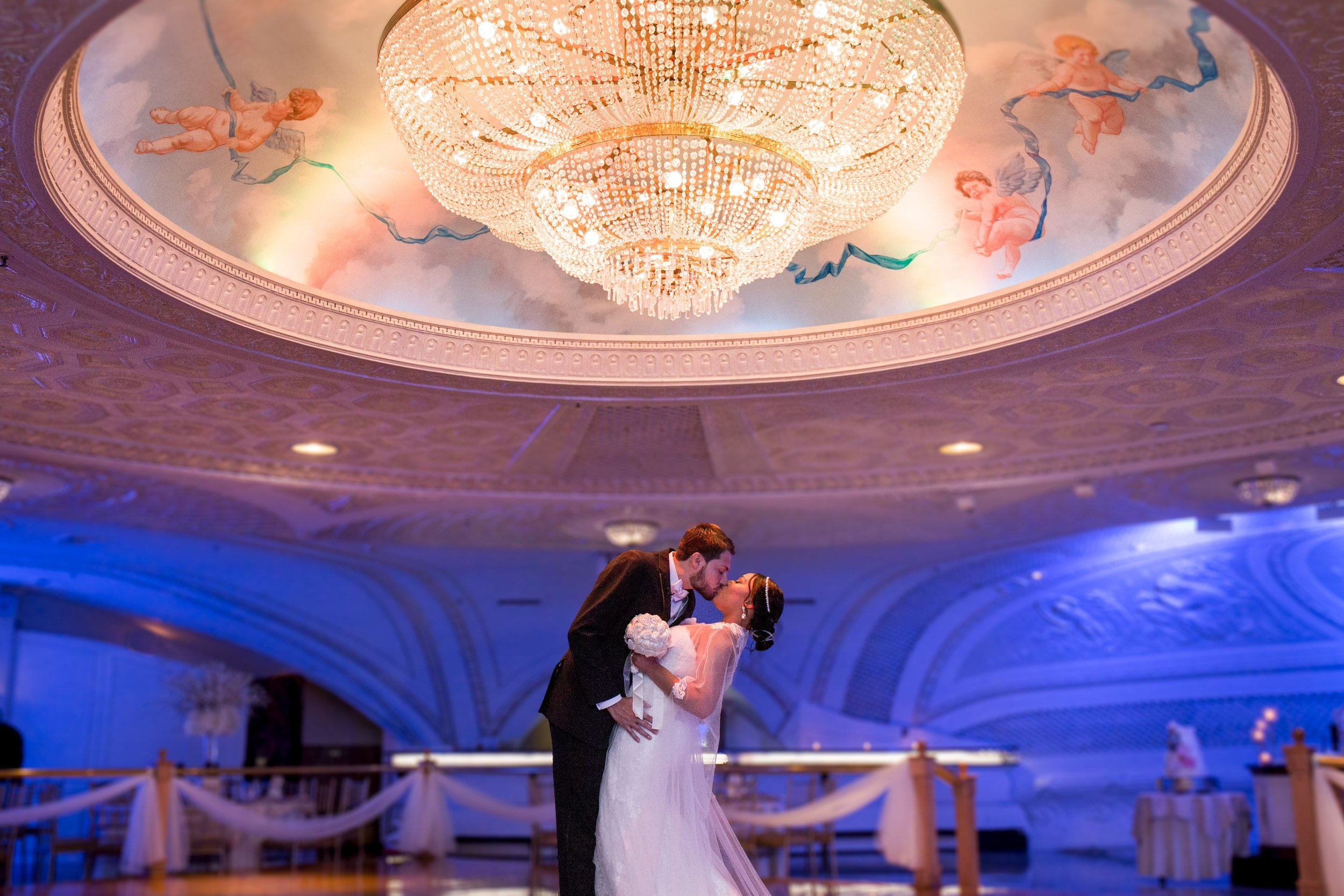 Bride and groom kissing in a ballroom under a large chandelier.