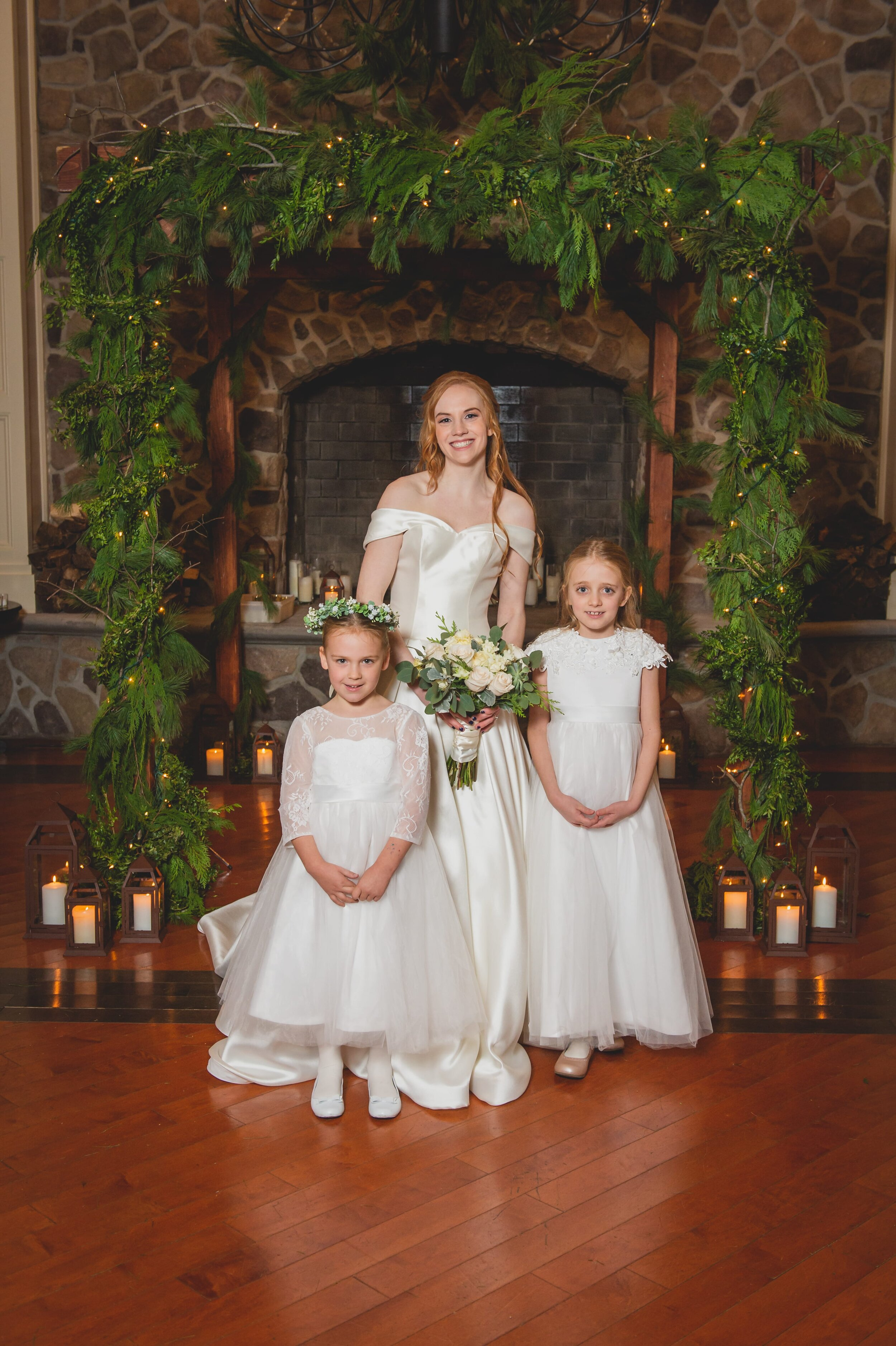 Bride with her 2 young nieces in front of a stone fireplace.