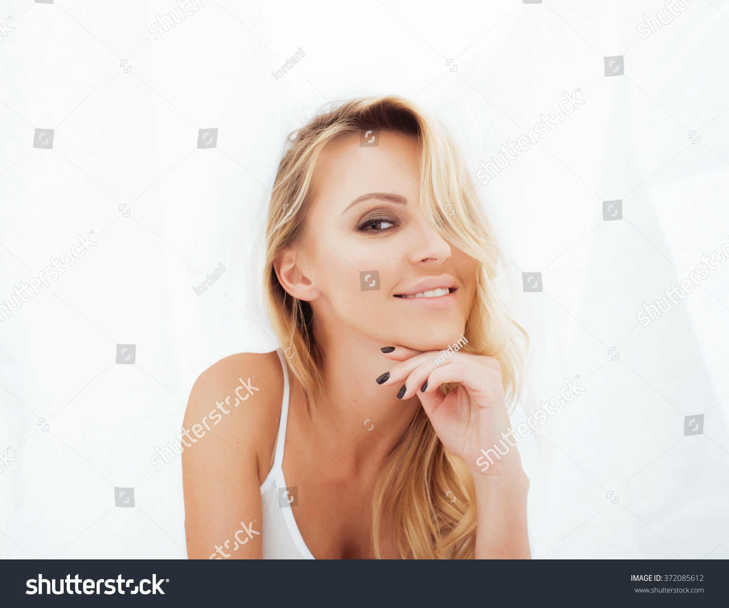 stock-photo-young-pretty-blond-woman-in-bed-covered-white-sheets-smiling-cheerful-sexy-look-close-up-372085612.jpg