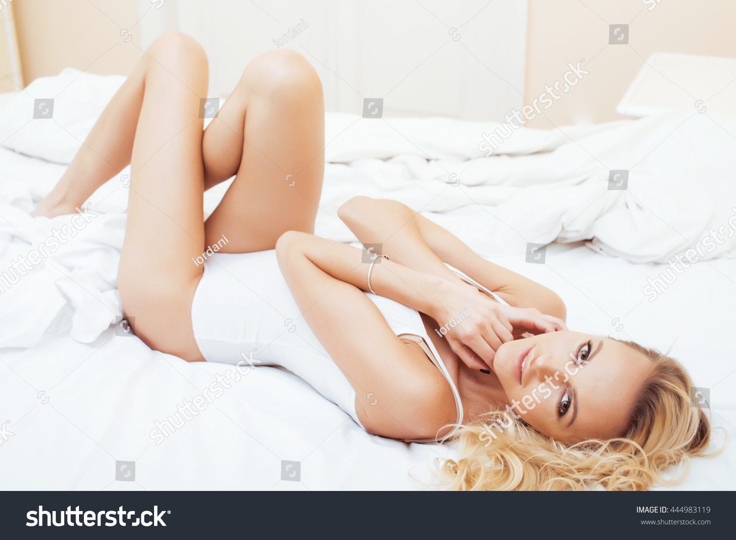 stock-photo-young-pretty-blond-woman-in-bed-covered-white-sheets-smiling-cheerful-sexy-look-close-up-happy-444983119.jpg