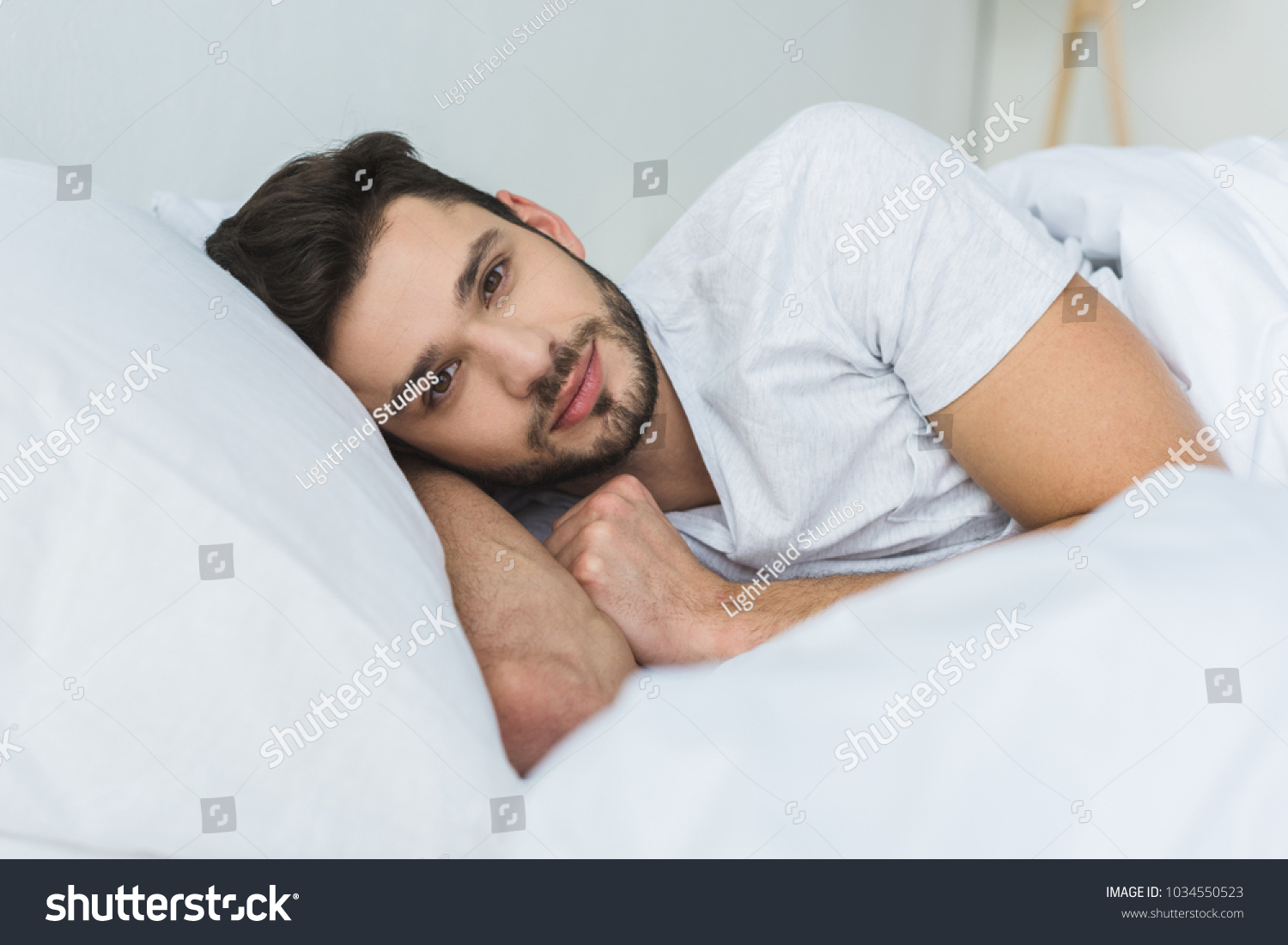 stock-photo-handsome-man-lying-on-bed-and-looking-at-camera-in-the-morning-1034550523.jpg