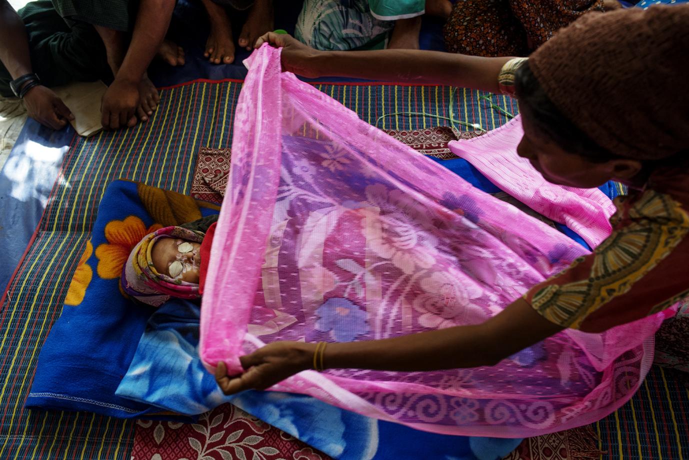 Rohingya mother sweeps a blanket over her deceased son, Sittwe, Rakhine / Burma - 2013