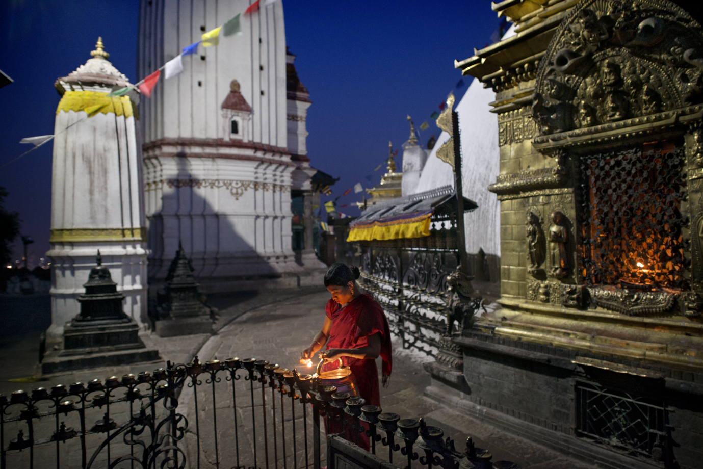 Women lighting candles at Swayambhunath Buddhist stupa, Kathmandu/ Nepal