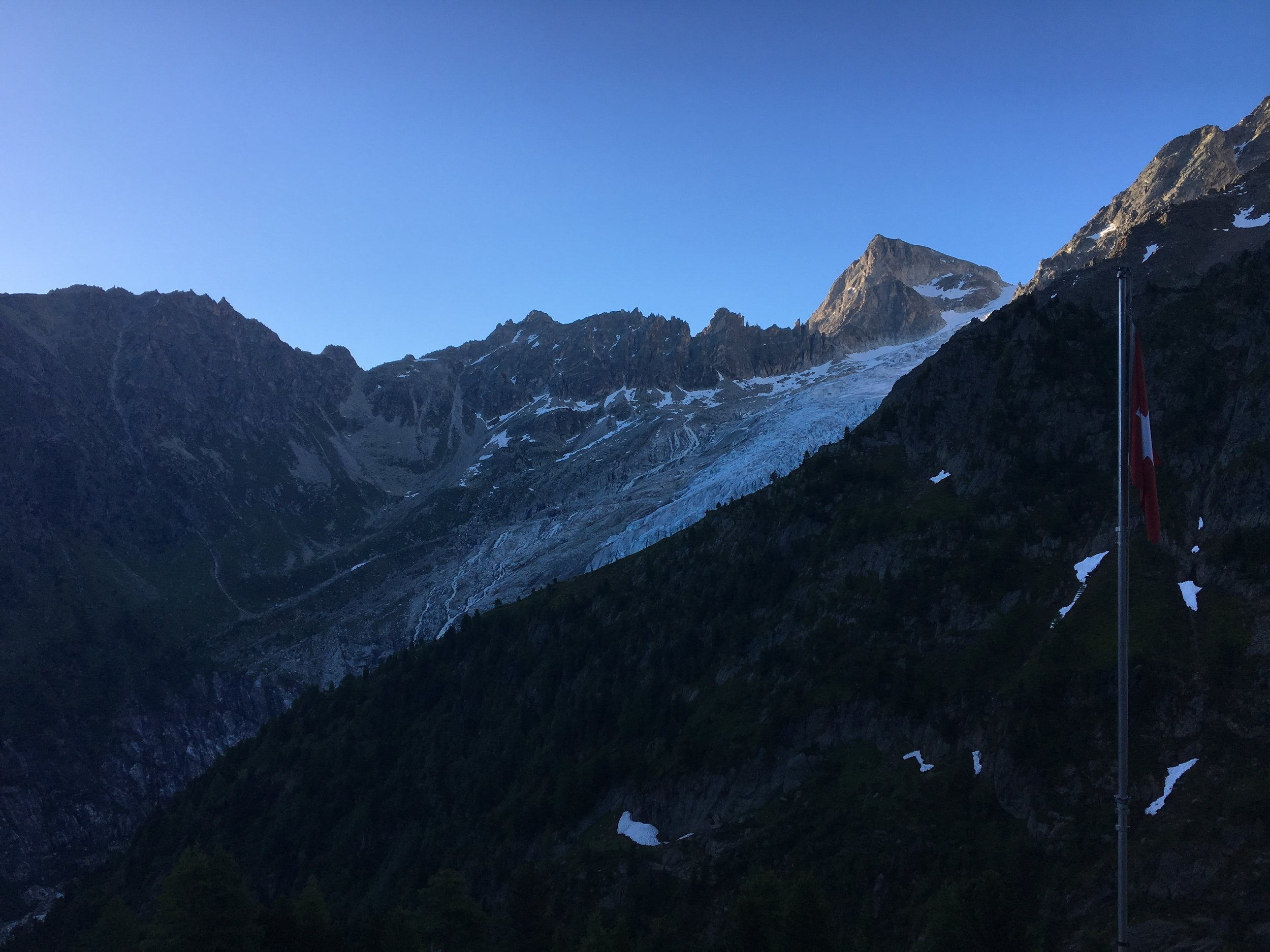 View from Refuge Les Grands of Glacier De Trient running down the valley with the difficult mountain pass of Fenetre d'Arpette located in the dip on the left side of the ridge