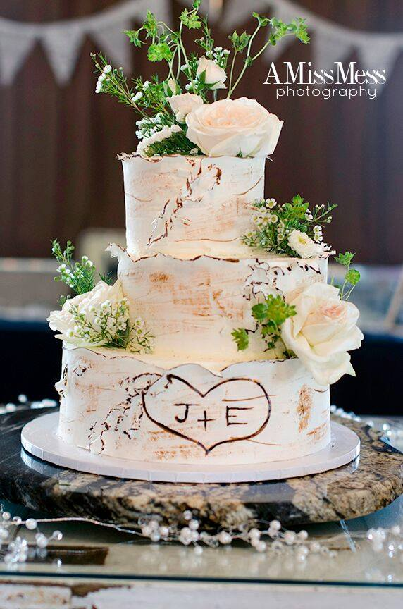 Rustic Style Wedding Cake - Creams & browns, topped with baby's breath flowers, and a rustic distressed icing touch.