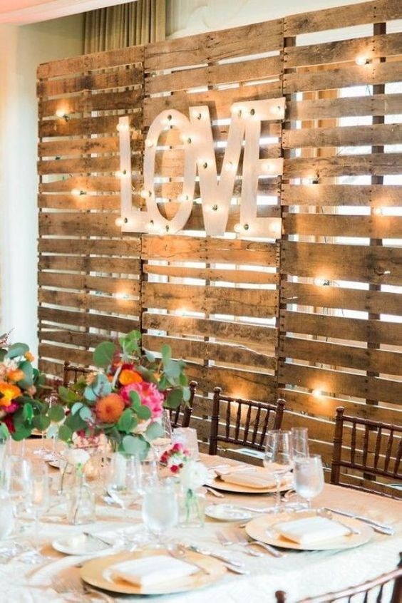 Wood & Cream with multi-colored Flowers - Cream tablecloth, wooden backdrop with a statement sign, colorful spring flowers in crystal vases.