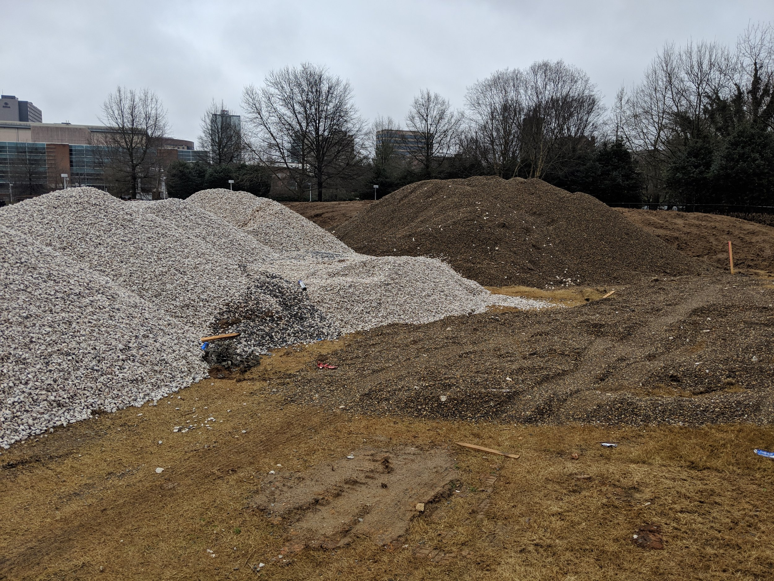 New gravel is stockpiled adjacent to gravel salvaged from the site during demolition.  These stockpiles will be used around the lawn's under-drain system.