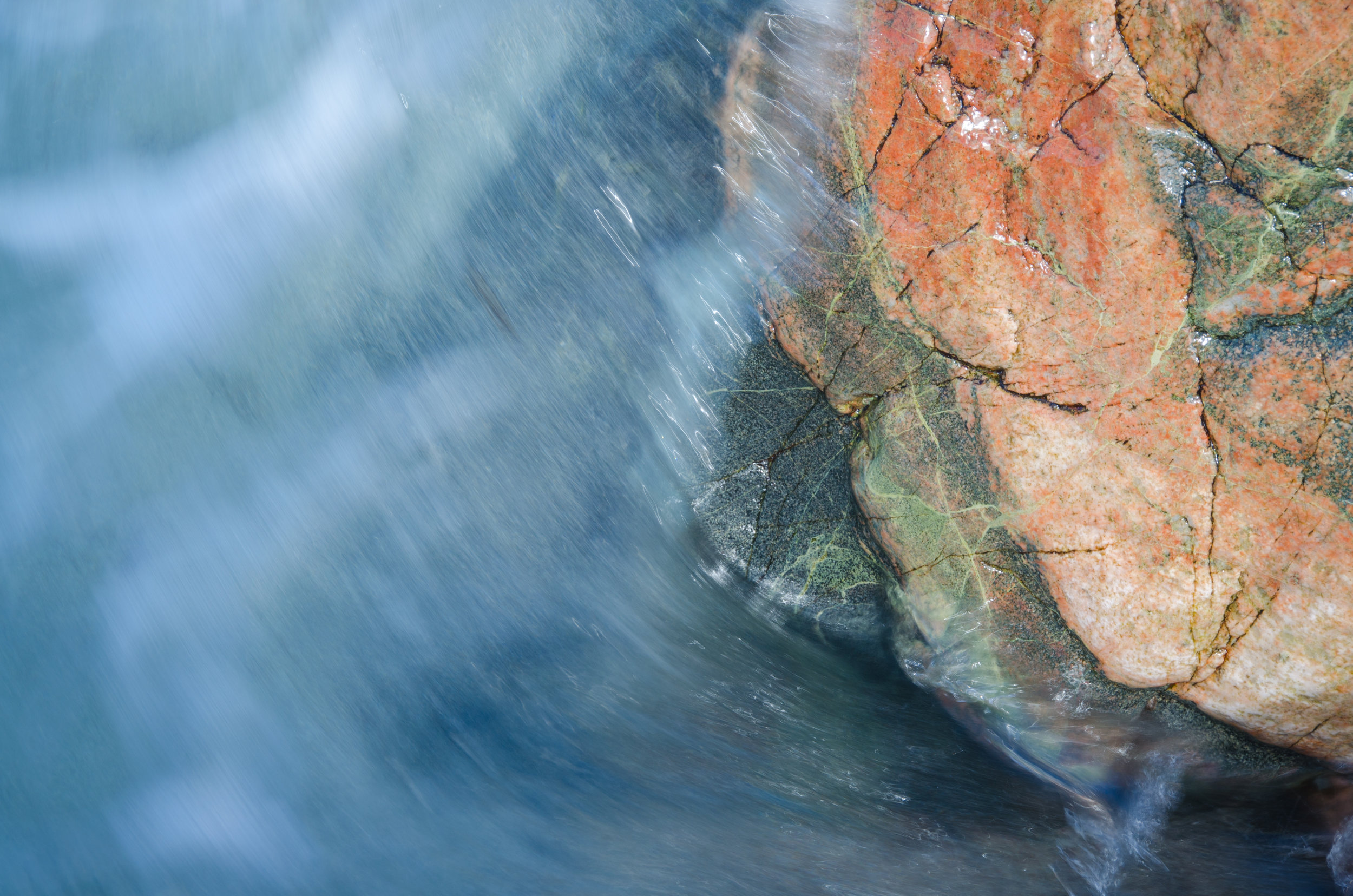 Water rushes over one of the colourful rocks