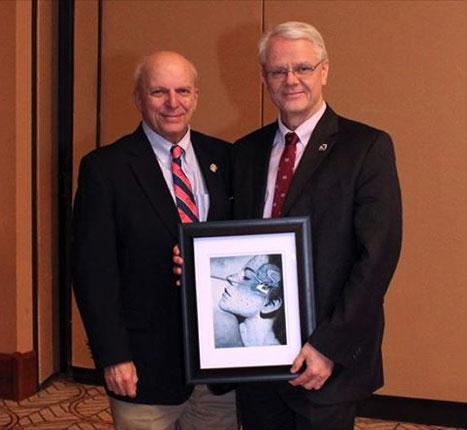 Dr. Rutka (right) presents original biomedical art to Dr. Weiss