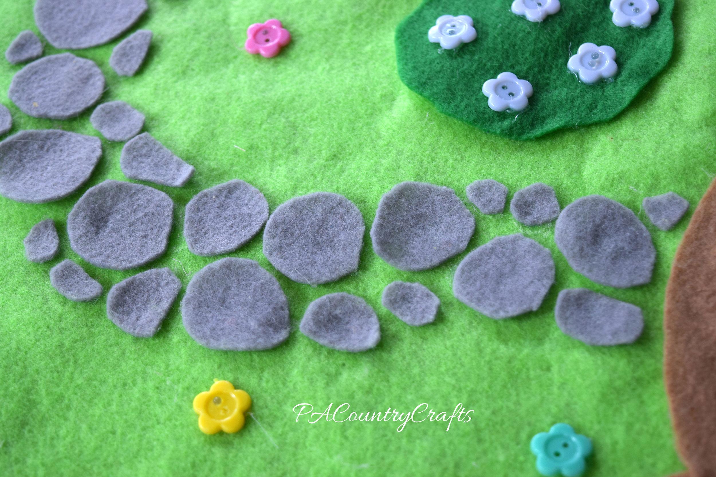 Make a felt cobblestone path by hot gluing gray circles onto felt