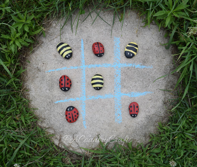 Ladybug and bumblebee painted rocks for an outdoor tic tac toe game