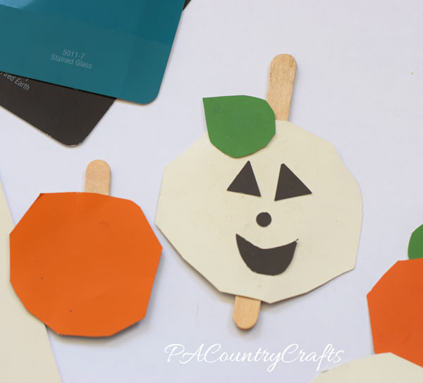 Preschool craft- jack o' lanterns made from paint chips and popsicle sticks!