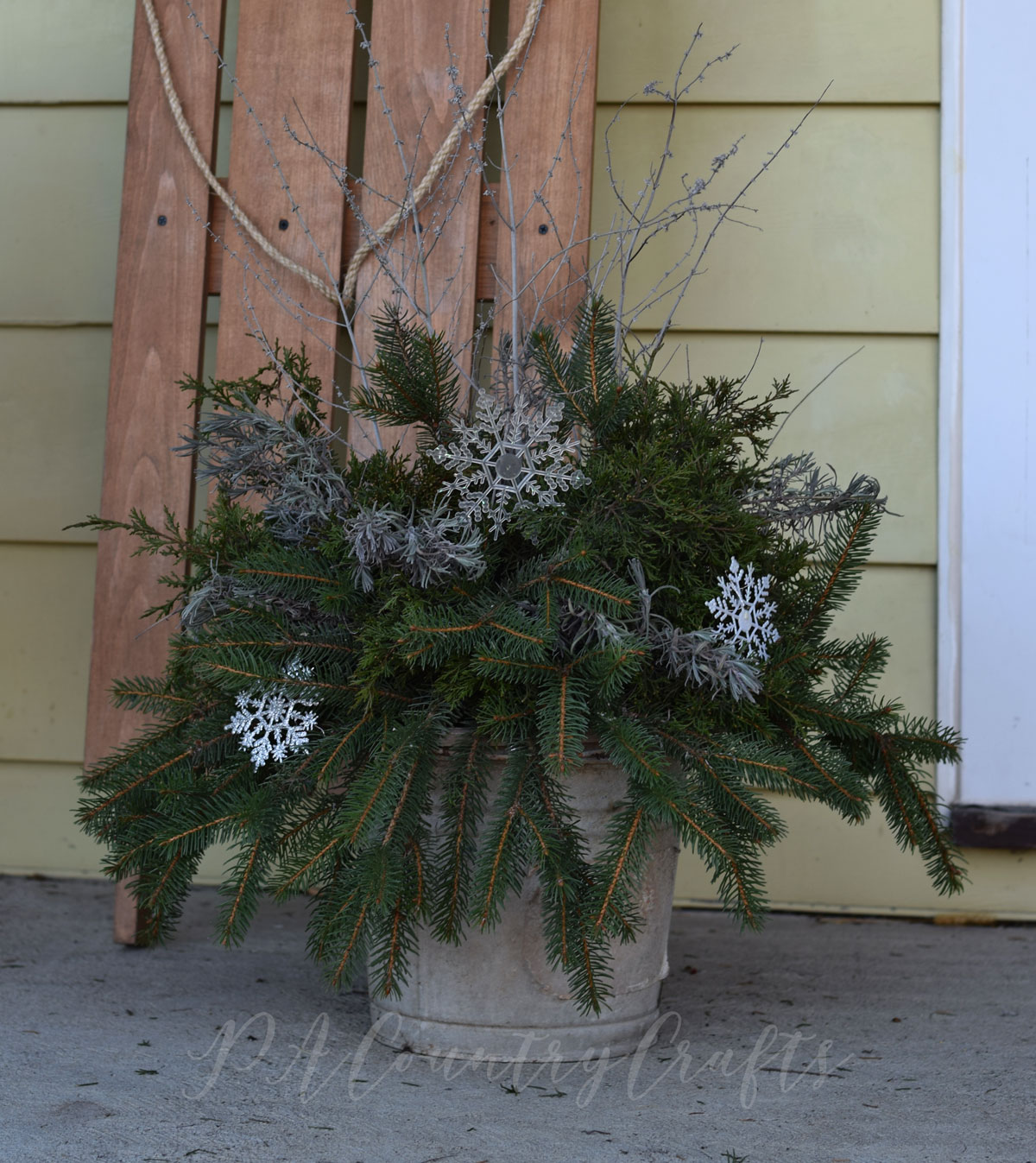 free winter planter made with greens and flower trimmings