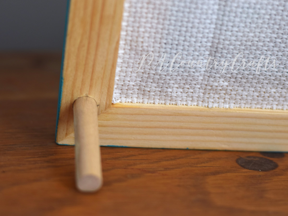 Dowels behind a simple wood frame so that it stands but the back is still accessible!