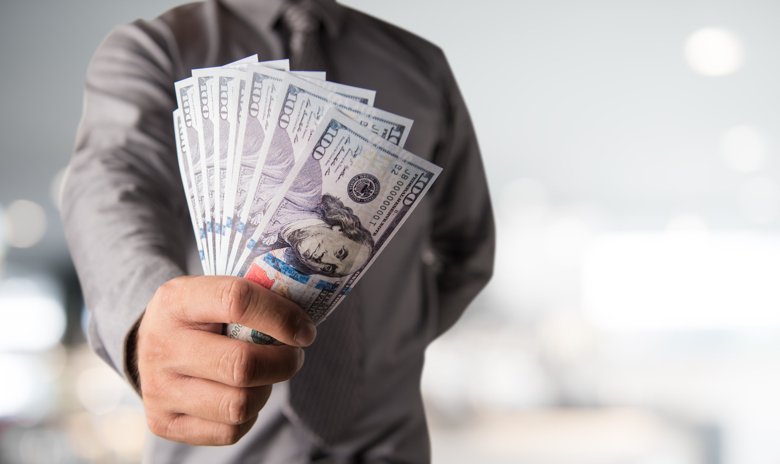 Canva - Businessman with money in hand, US dollar (USD) bills - investment, success and profitable business concepts.jpg