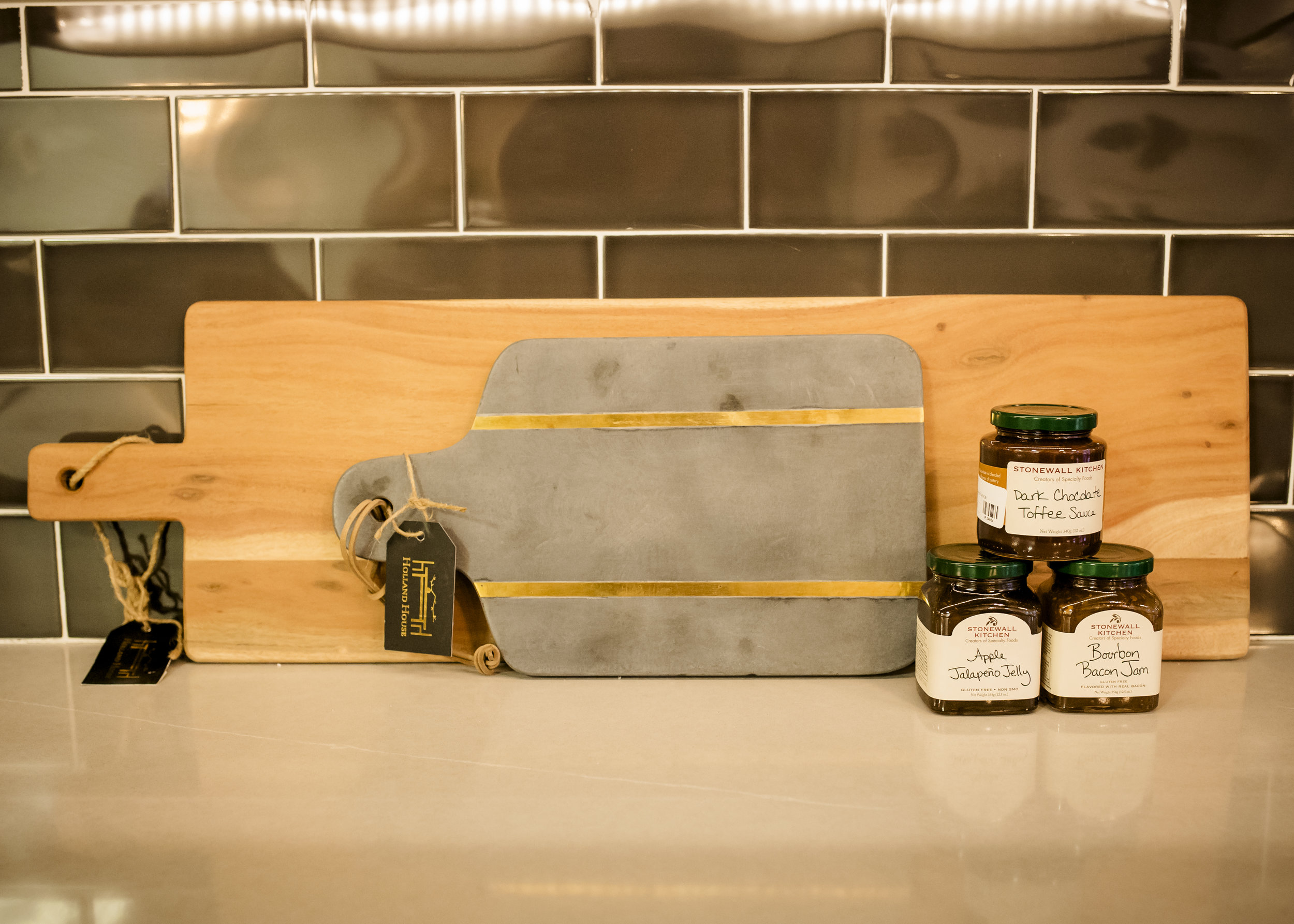 Oversized Wood Cutting Board $100, Gray Glimmer Cutting Board $45, Dark Chocolate Toffee Sauce $8, Apple Jalapeño Jelly $8, Bourbon Bacon Jam $8