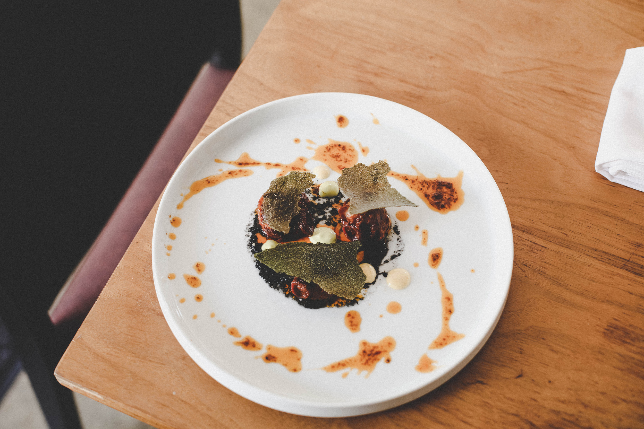 Chorizo octopus with burnt onion pure, chilli sauce, and cassava crackers.