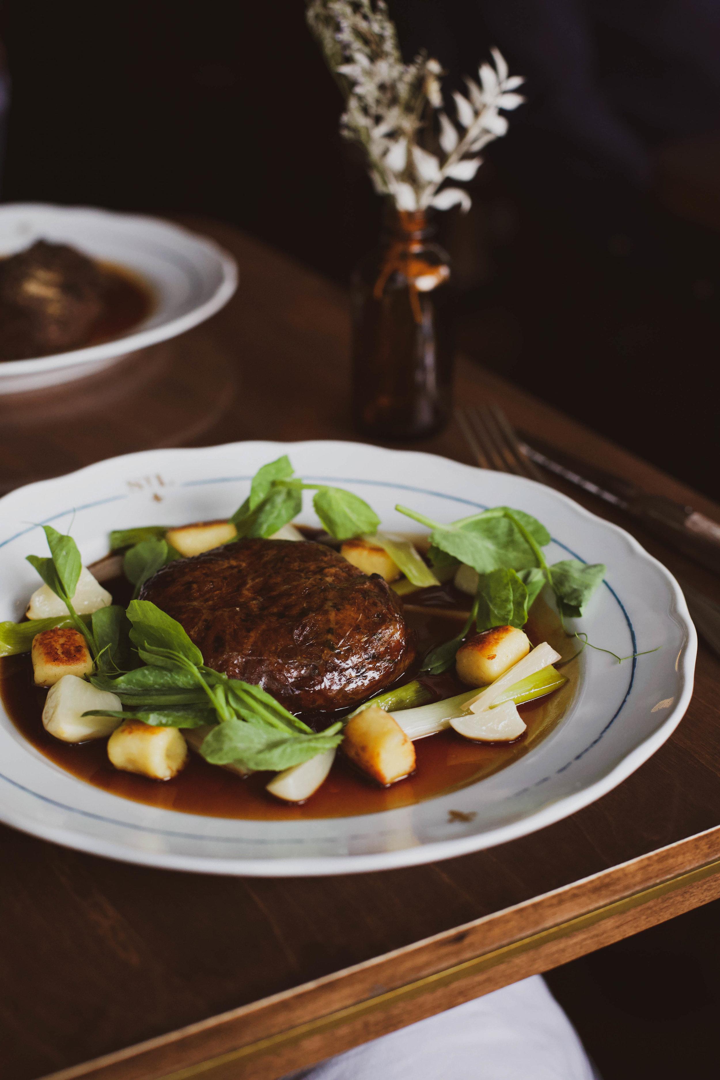 Braised lamb shoulder, Parisian gnocchi & summer greens