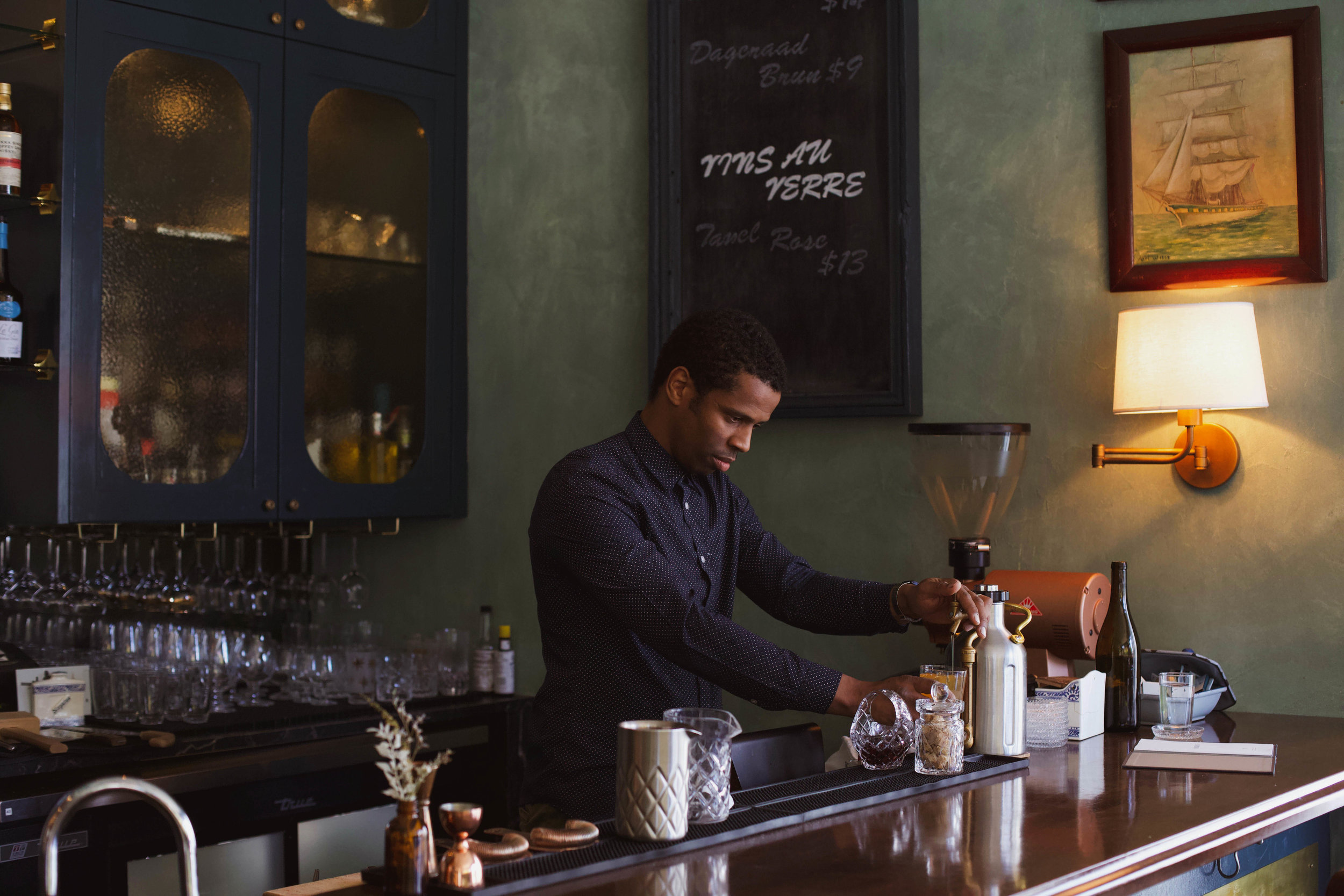 Head bartender Yacine Sylla pours house-made iced tea from his mini growler keg