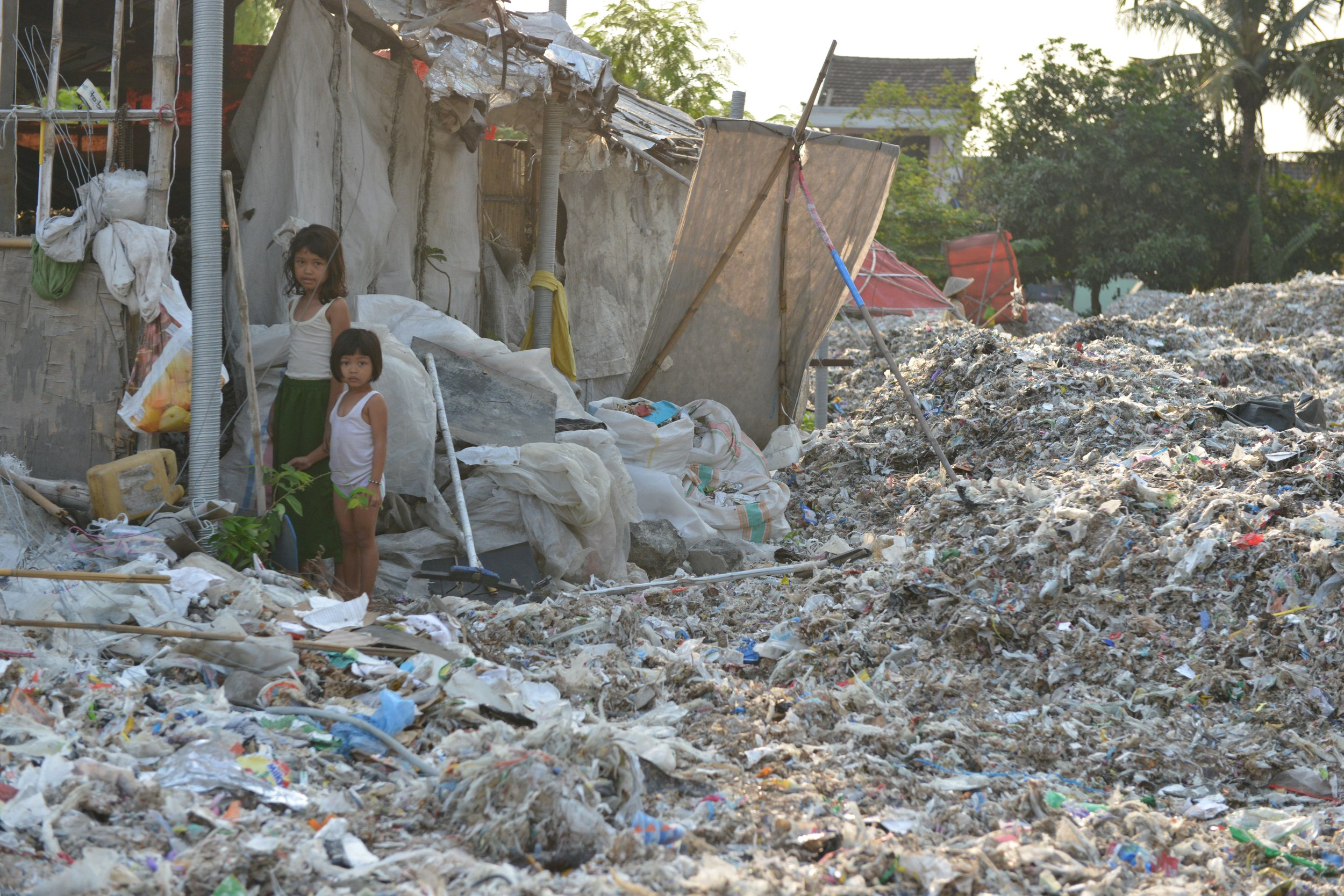 Children in Indonesia amid a field of plastic waste, all imported from the US, EU, and other Western nations.