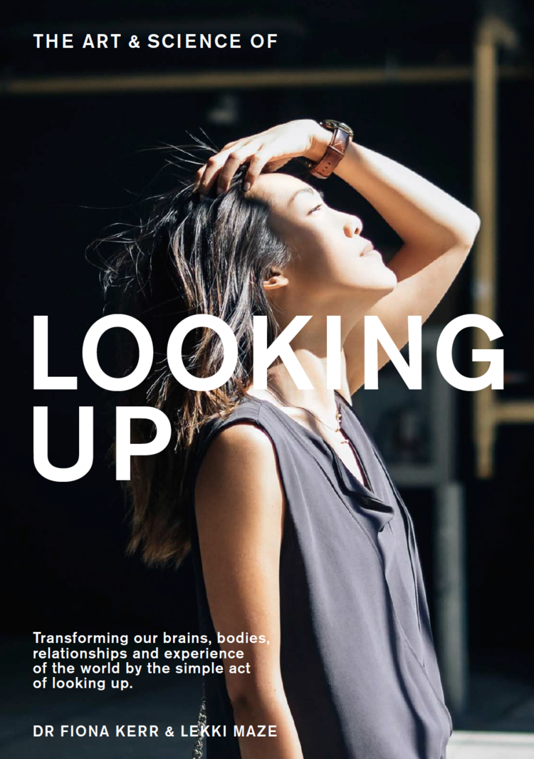 Woman with long dark hair holds it back as she turns her face up to the sun. The words 'Looking Up' are emblazoned across her in capital font