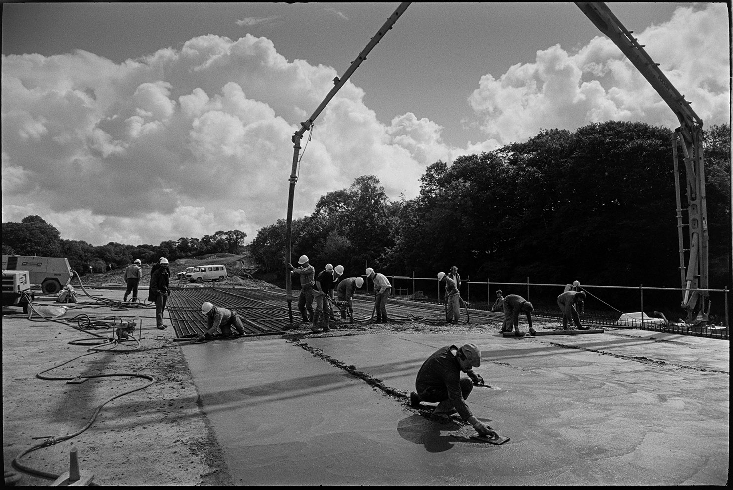 Men building new link road laying cement delivered by crane, near South Molton, August 1988