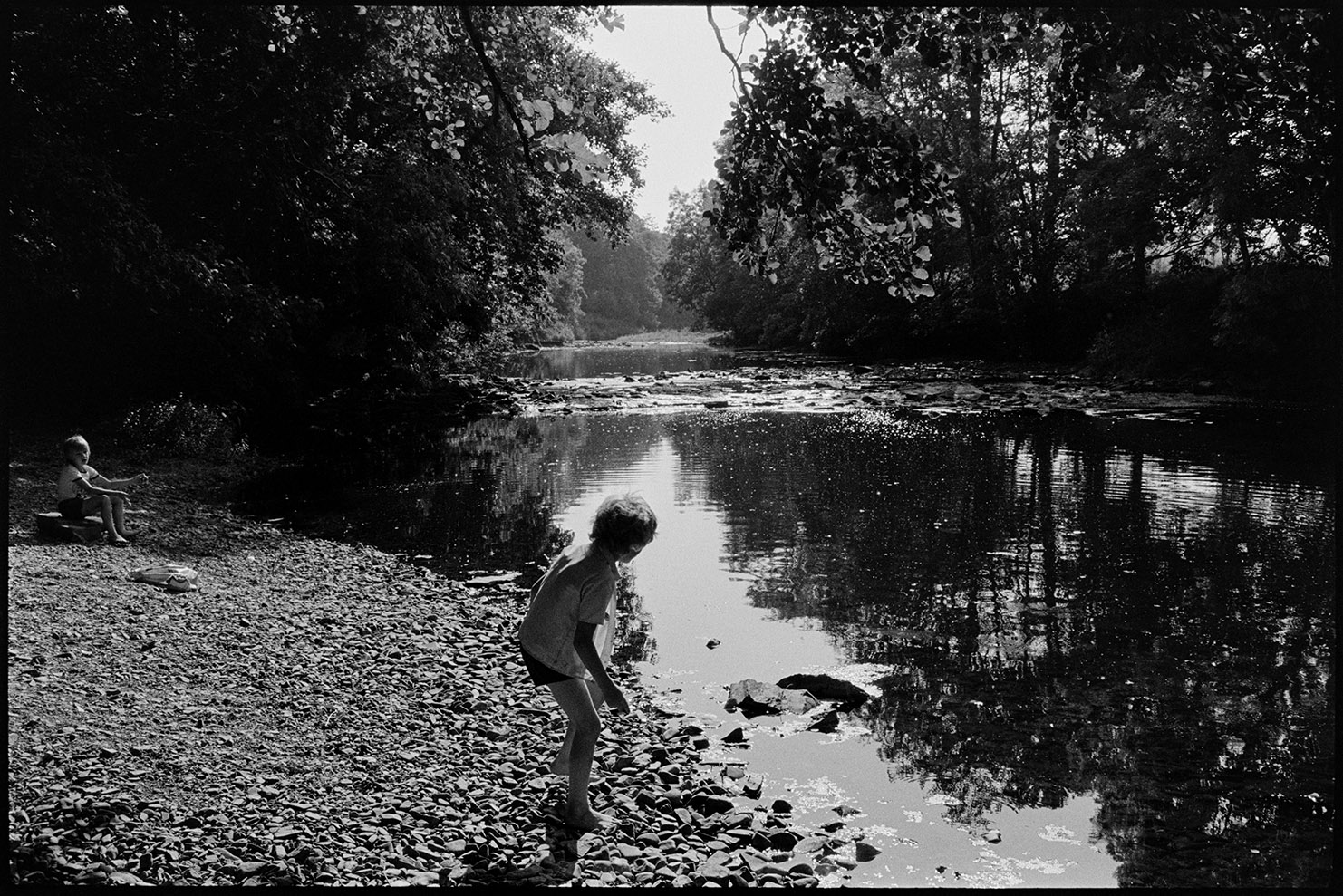 Children beside river, skimming stones Dolton, Halsdon, August, 1976.