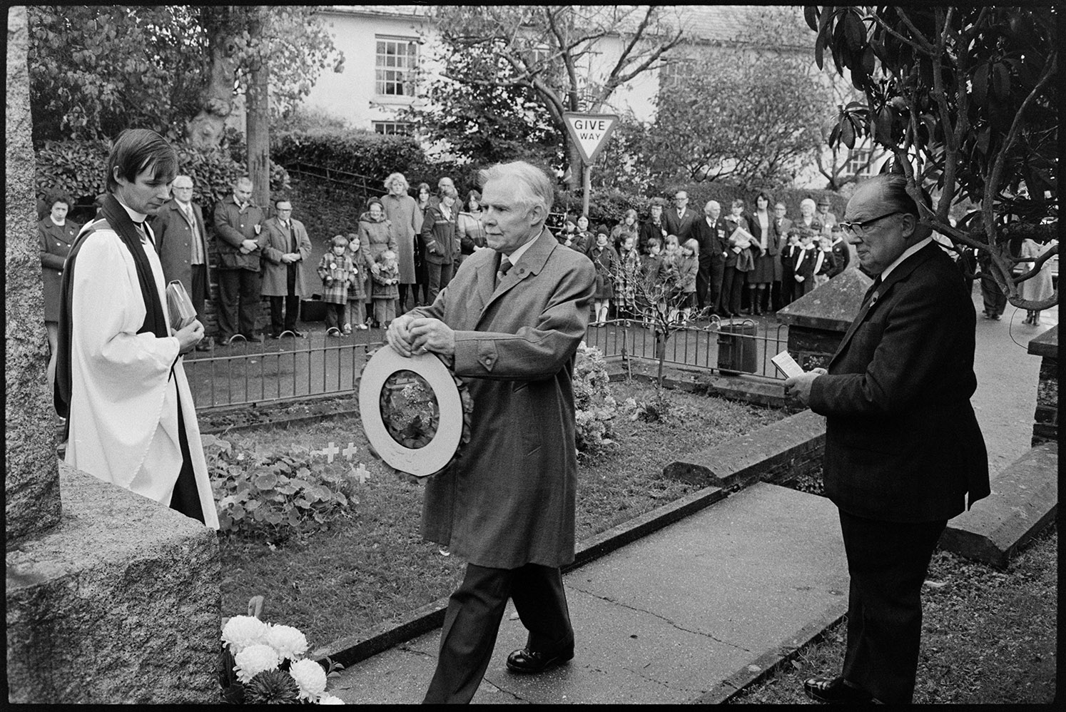 Remembrance Day ceremony at village war memorial, old soldiers with poppy wreath.  Dolton, 11 November 1979