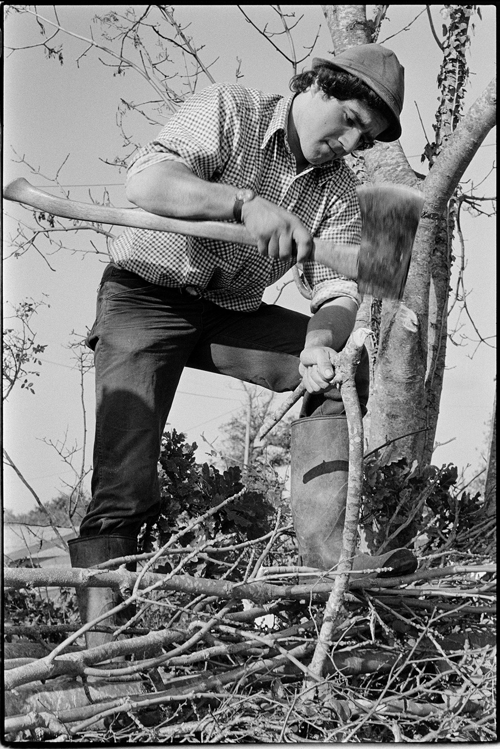 Man hammering wooden cruck into place using axe-head – Stephen Squire, Dolton, Lower Langham, October 1978. Documentary photograph by James Ravilious for the Beaford Archive © Beaford Arts